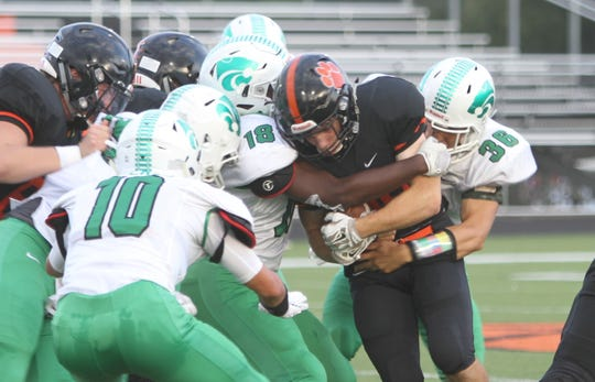 Brighton running back Chris Seguin is tackled by Novi's Jason Jennings (18) and Matthew Wright (36) during the Bulldogs' 38-0 victory on Thursday, Aug. 30, 2018.