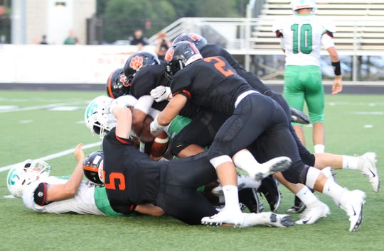 Linebackers Cole Riddle (5) and Zach Pardonnet (2) are part of a Brighton defense that swarms Novi's Jason Jennings in a 38-0 victory on Thursday, Aug. 30, 2018.