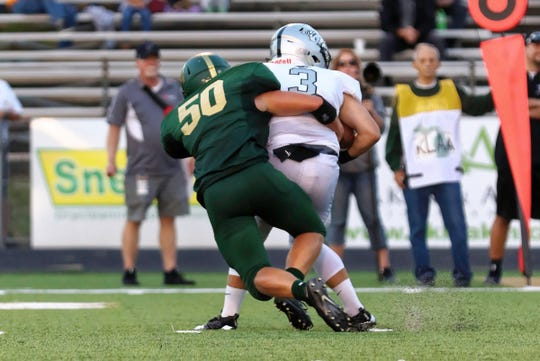 Howell's Philip Pietila sacks Plymouth quarterback Nick Downs in the Highlanders' 26-17 loss on Thursday, Aug. 30, 2018.