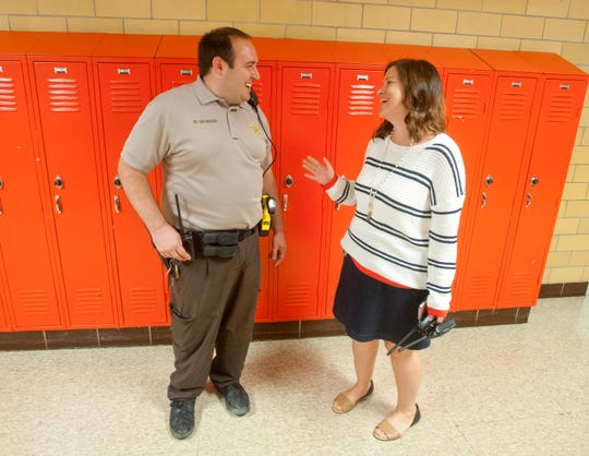 Fern Creek High School Resource Officer Robbie Skaggs is a Jefferson County deputy sheriff. Here he chats in the hallway with school principal Rebecca Nicholas.