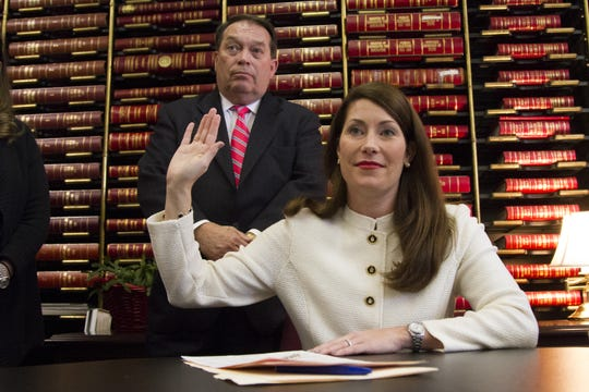 Kentucky Secretary of State Alison Lundergan Grimes takes an oath alongside her father, Jerry Lundergan, after filing for re-election in 2015.