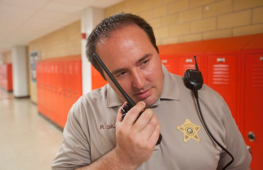 Fern Creek High School Resource Officer Robbie Skaggs is a Jefferson County deputy sheriff speaks to one of the school's security team on his radio.August 31, 2018