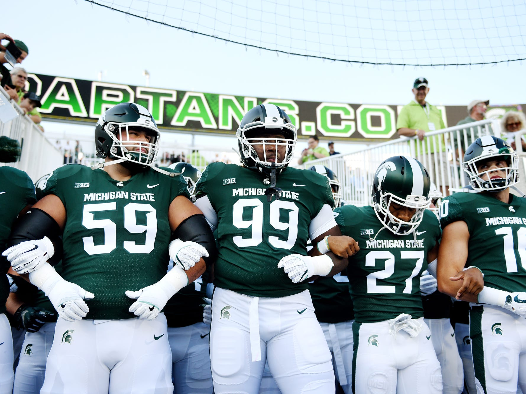 Michigan State players, from left, David Beedle, Raequan Williams, Khari Willis and Matt Morrissey lock arms before taking the field for warm ups before the Spartans' game against Utah State on Friday, Aug. 31, 2018, at Spartan Stadium in East Lansing.