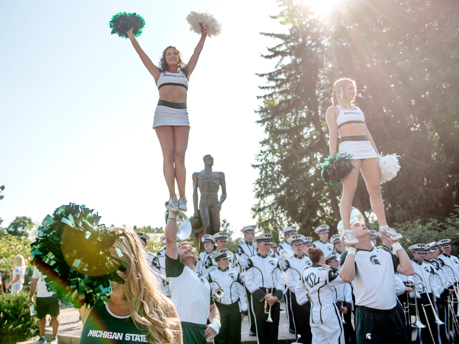 Michigan State University cheerleaders perform for fans at the Sparty statue before the Spartans' game against Utah State on Friday, Aug. 31, 2018, in East Lansing.