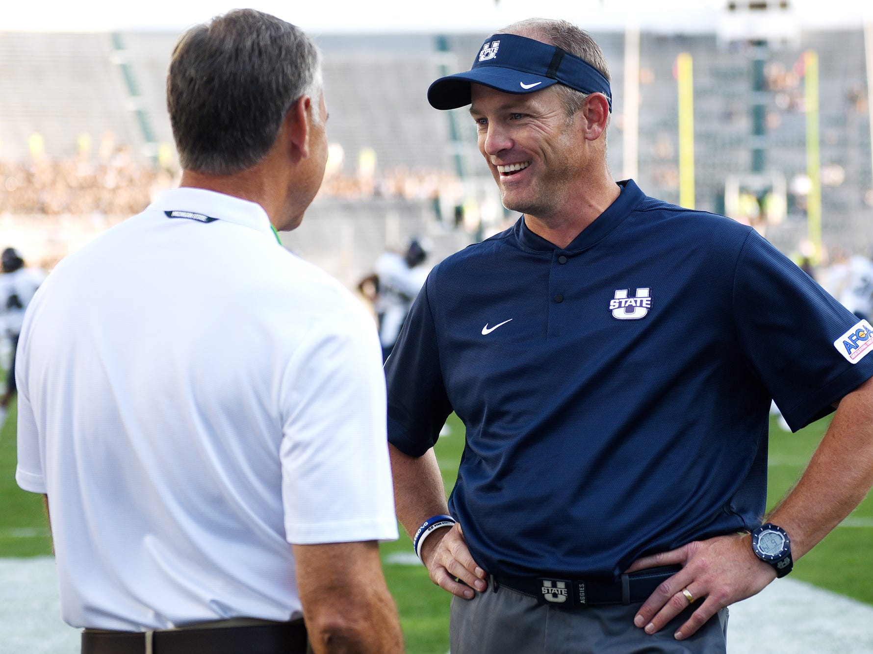 Utah State head coach Matt Wells, right, talks with MSU head coach Mark Dantonio before their game on Friday, Aug. 31, 2018, at Spartan Stadium in East Lansing.