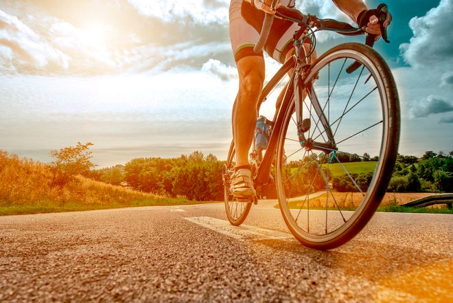 Close up of a athlete who rides his bike up a steep hill. The sun shines as his feet hits the pedals and he drives the bicycle forward.