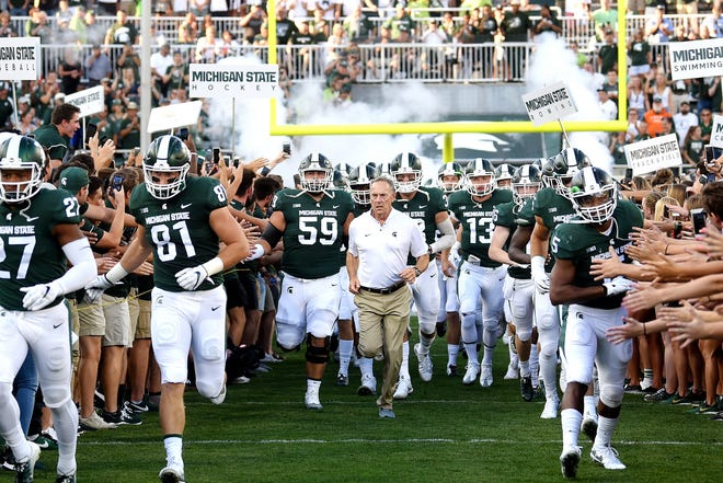 The Michigan State Spartans take the field before the start of their game against Utah State on Friday, Aug. 31, 2018, at Spartan Stadium in East Lansing.