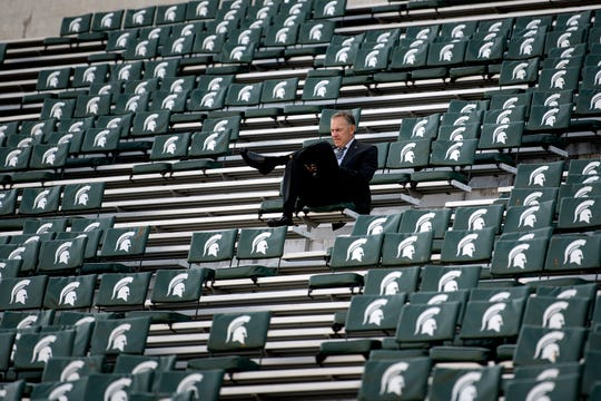 MSU coach Mark Dantonio sits alone in the stands at Spartan Stadium earlier this season.
