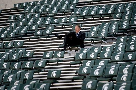MSU coach Mark Dantonio sits alone in the stands at Spartan Stadium earlier this season.