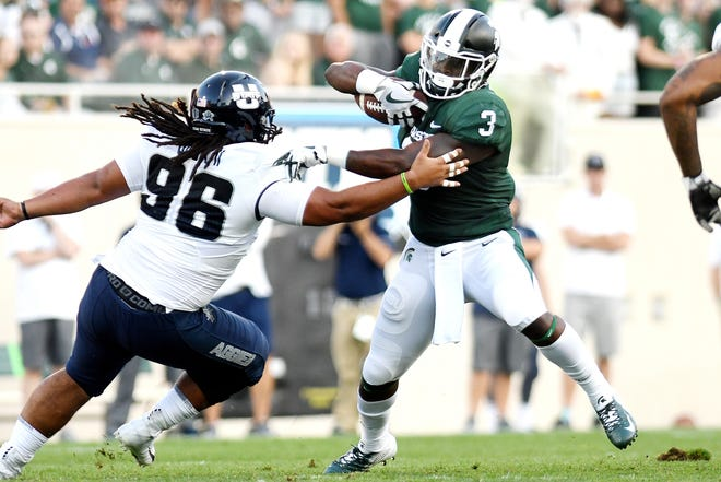 Michigan State's LJ Scott, right, runs with the ball as Utah State's Christopher 'Unga closes in during the first quarter on Friday, Aug. 31, 2018, at Spartan Stadium in East Lansing.