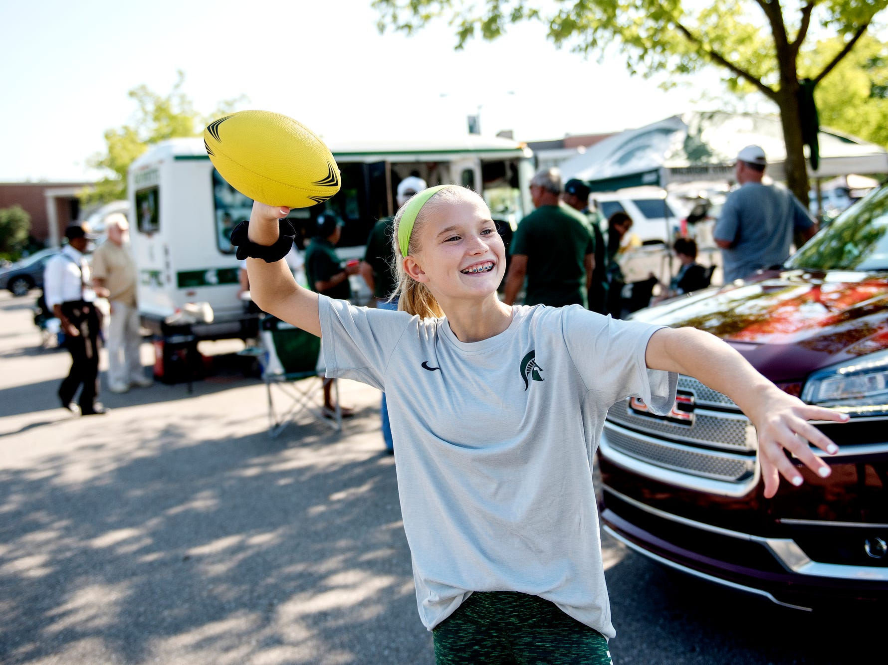 Claire Casey, 11, of Okemos, throws a football to her father Jeff while tailgating before the Spartans' game against Utah State on Friday, Aug. 31, 2018, in East Lansing.