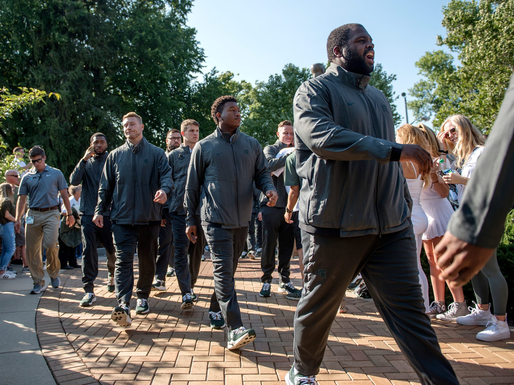 The Michigan State University football team walks by fans at the Sparty statue on campus before the Spartans' game against Utah State on Friday, Aug. 31, 2018, in East Lansing.