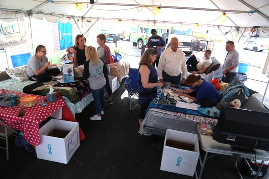 Participants of the the Great Sleep-Out Against Domestic Violence prepare to compete at Johnn'y Mattress and Furniture Superstore on Thursday.