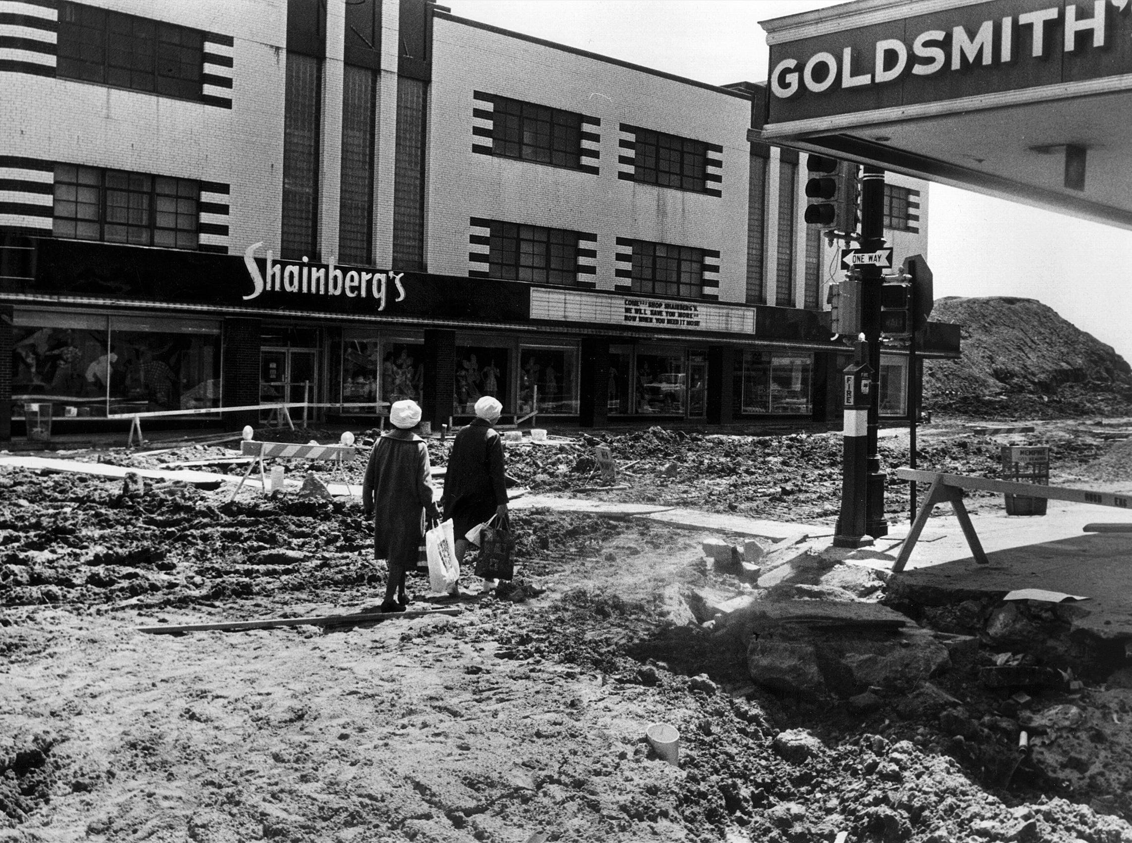 The going was not so easy for these Main Street shoppers, walking south of Gayoso at Goldsmith's and Shainberg's in April 1975. The Mid-America Mall was under construction and the once busy street was more like a battle zone than a street during construction.