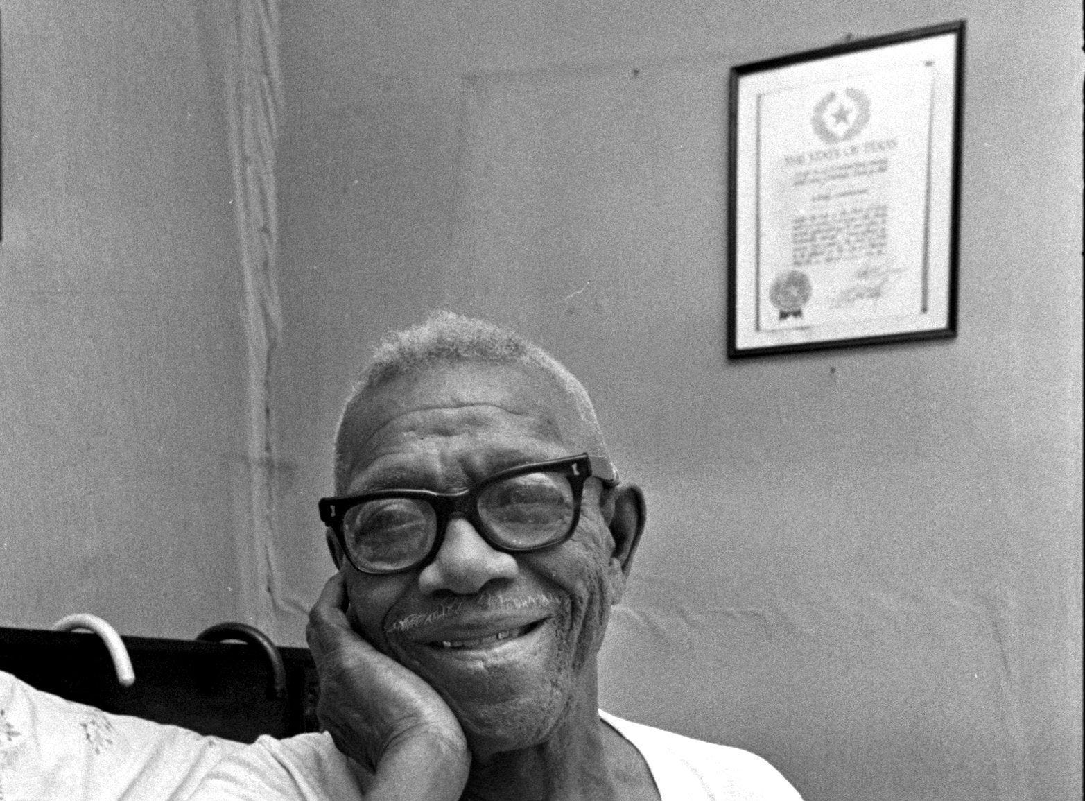Furry Lewis, legendary Memphis bluesman, in the bedroom of the Memphis duplex at 811 Mosby where he had lived for six years. Age 83 at the time (August 13, 1976), Lewis suffered from cataracts and said he couldn't see anything but shadows.