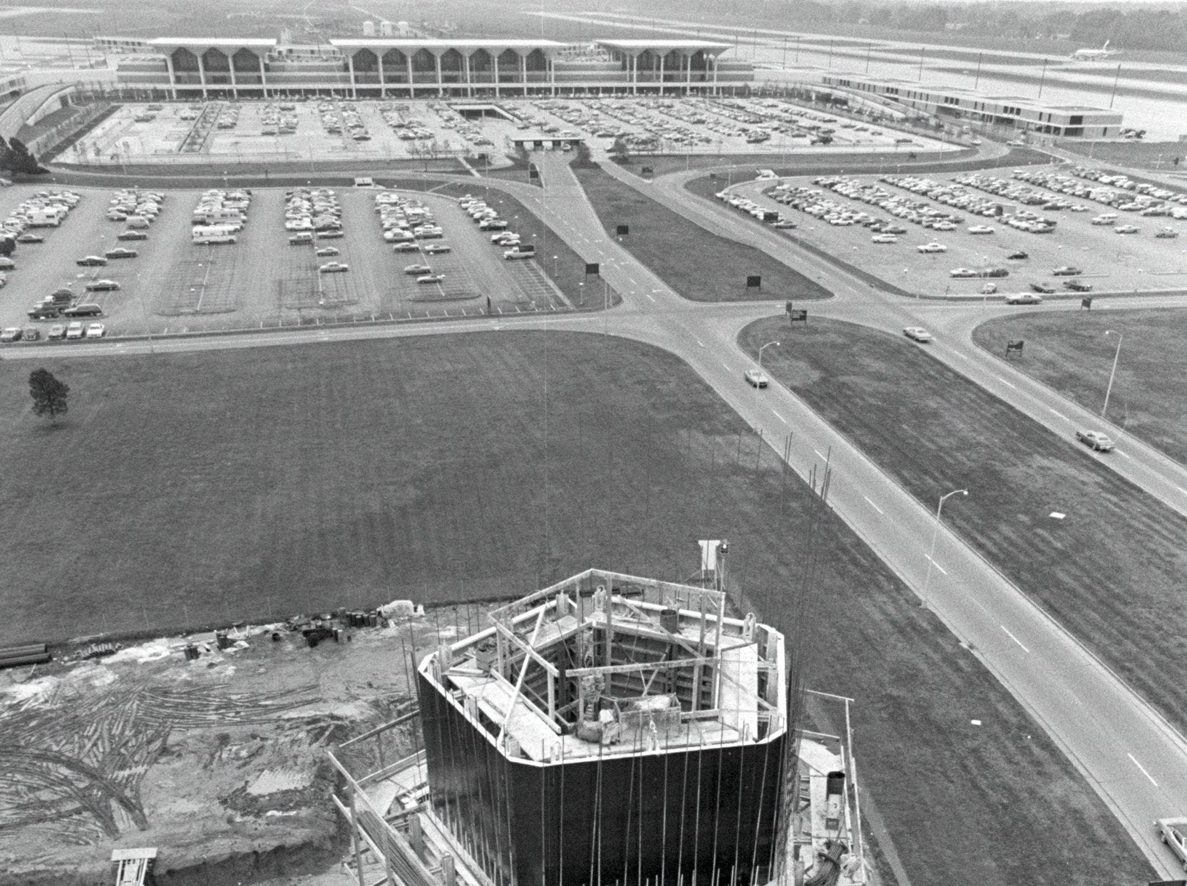 The new air traffic control tower at Memphis International Airport, which will replace an overcrowded tower with some obsolete equipment, stretched 100 of its eventual 185 feet on 7 Nov 1975. It is scheduled to be completed in June and operational a year later with the most sophisticated electronic equipment. Its cost is about $2.5 million, entirely federally financed. The design is the standard one the Federal Aviation Authority is using now on all airports. The picture was taken from a 150-foot crane alongside the rising tower.