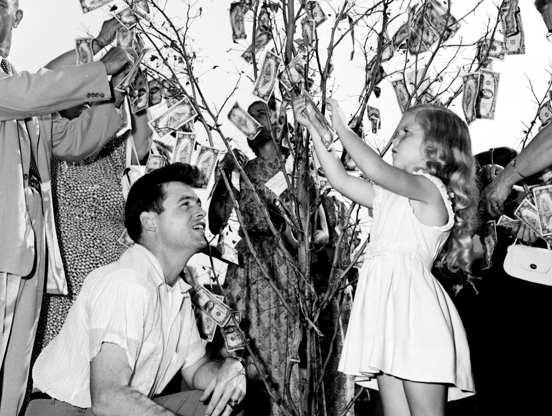 To disprove an old saying and to swell a building fund, McLean Baptist Church members of all ages made money grow on a tree on 9 Aug 1953. Taping on bills after the church?s ground-breaking ceremony were J. Keith Davidson of 773 Hawthorne and his 5-year-old daughter, Donna Davidson.