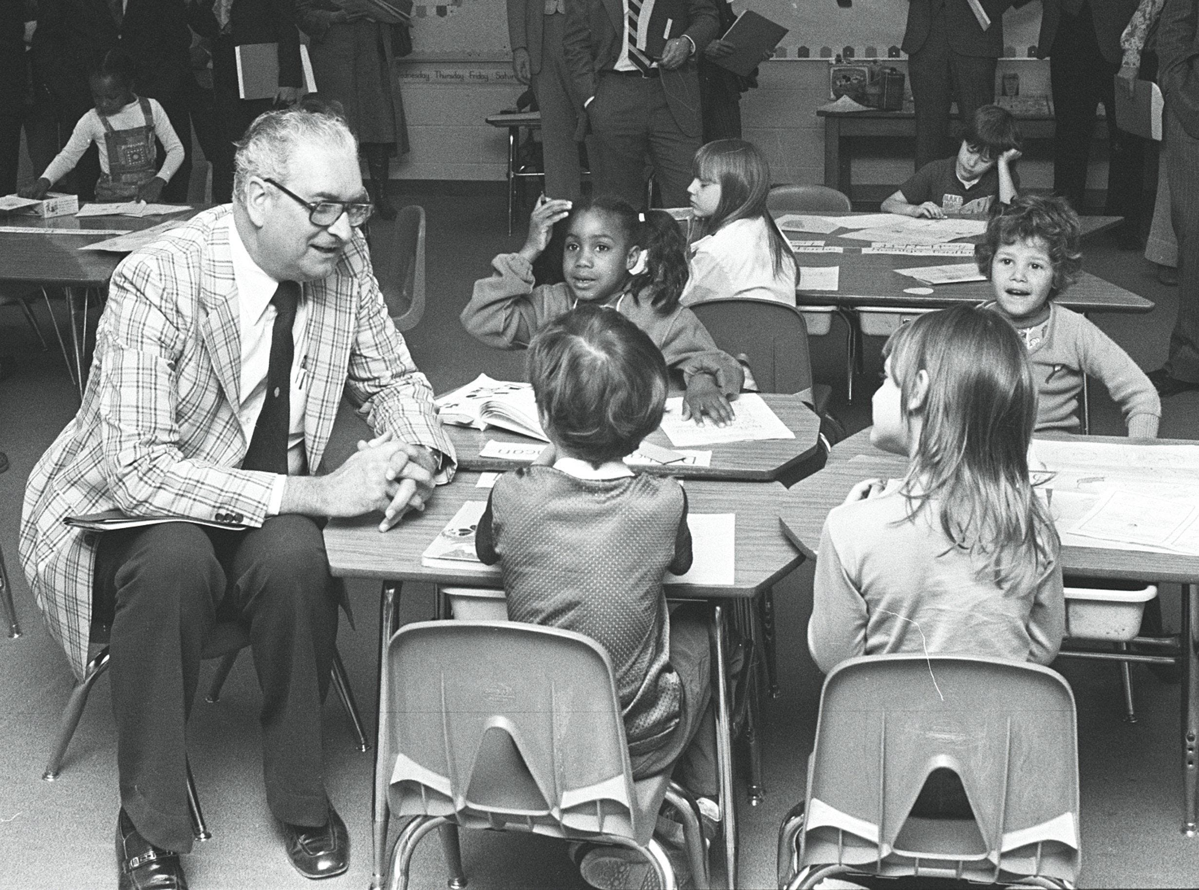 Memphis City Councilman Billy Hyman takes time on his tour of Sheffield Elementary school to talk with 6-year-old students Dion Donaldson and Kelly Caldwell (Backs to Camera) and DeSharon Duncan and Ricky Nicholson. Hyman was one of seven council members who toured several school offices and classrooms on 29 Mar 1978 to bring themselves up to date on the operation of the city school system.