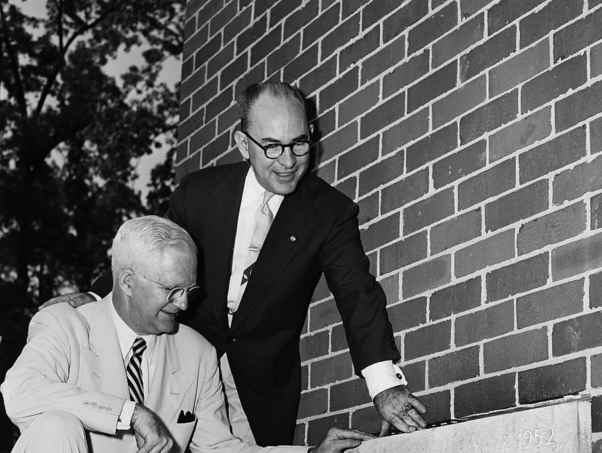 Members of Linden Avenue Christian Church set in place the material cornerstone of a $700,000 educational building and temporary sanctuary on 14 June 1953. Leaders included Dr. H.T. Wood, left, pastor, and J. Barrow Simmons, chairman of the executive committee new building council. The almost complete structure is at Union and East Parkway.