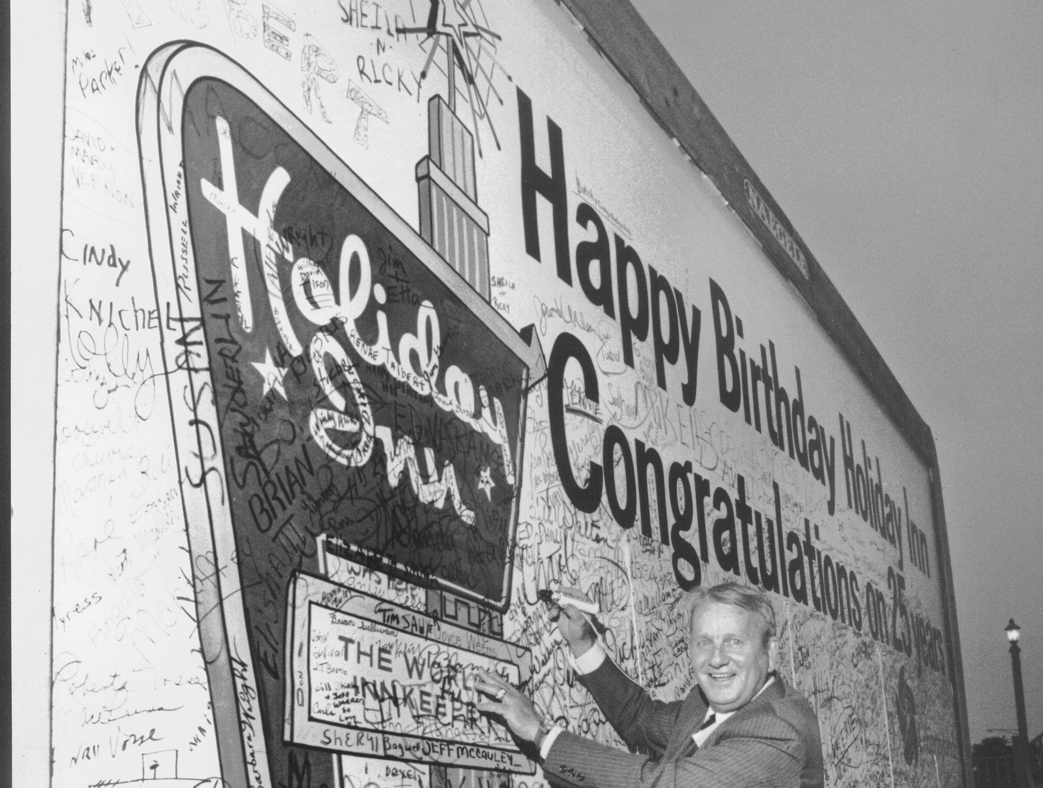 Dave Darnell/The Commercial Appeal Founder and chairman of the board Kemmons Wilson adds his name to a 12-by-25-foot card wishing Holiday Inns a happy 25th birthday on Sept. 8, 1977. More than 8,000 employees and their families' special guests were invited to a party at Libertyland to celebrate the event.