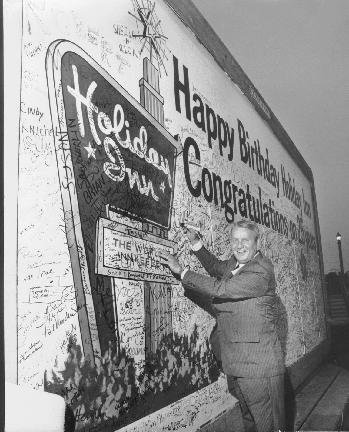 Founder and chairman of the board Kemmons Wilson adds his name to a 12-by-25-foot card wishing Holiday Inns a happy 25th birthday on Sept. 8, 1977. More than 8,000 employees and their families' special guests were invited to a party at Libertyland to celebrate the event.