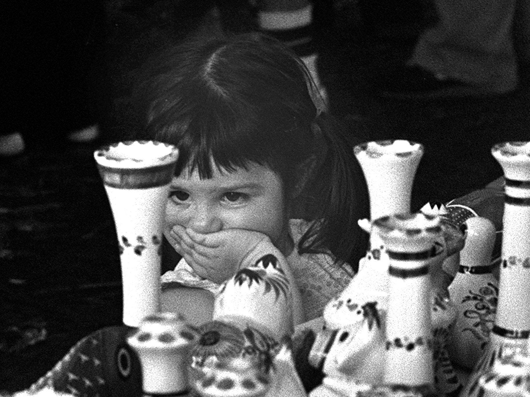 Two-year-old Julia Shaffer shops for pottery at Tom Lee Park during the Memphis in May Fiesta Mexicana on 6 May 1984. She appraised the objects, then tentatively decided to have her father, Frank Shaffer, buy her the figure of a dog.