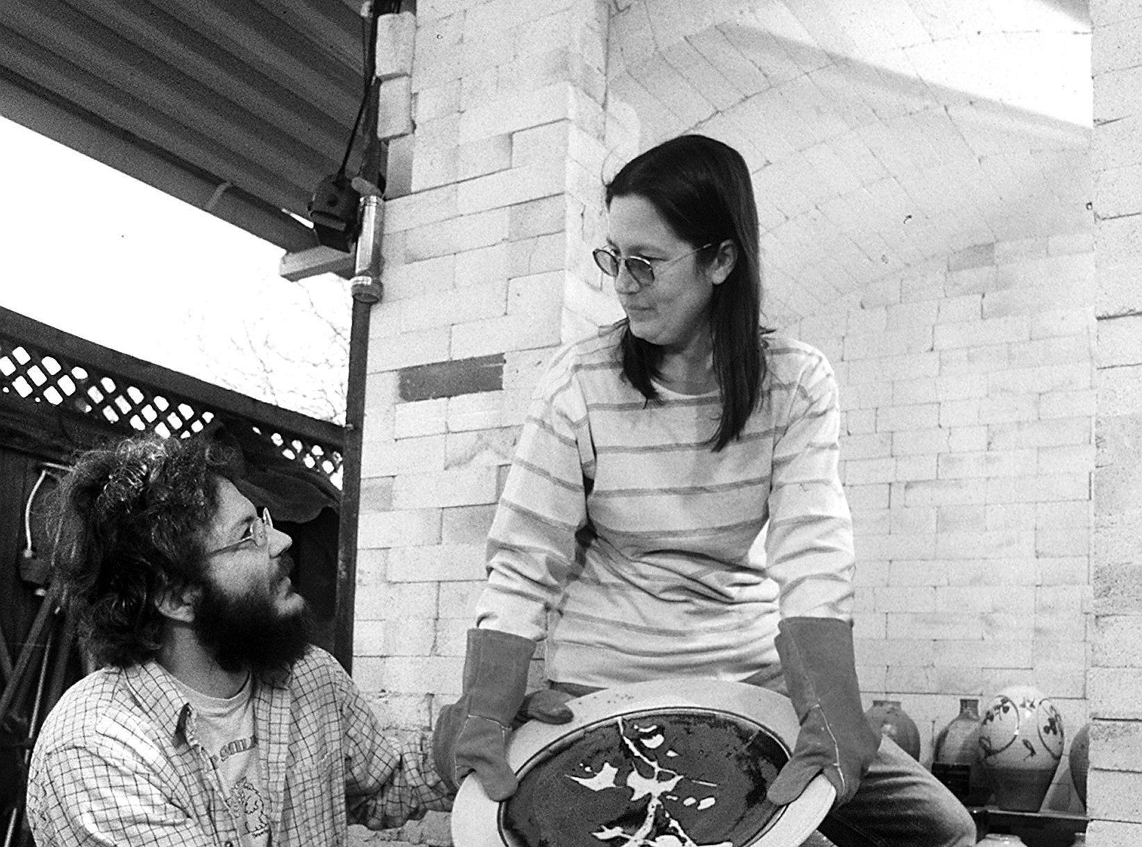 Dale and Brin Baucum at the kiln door in March 1985 prepare for the sixth annual Memphis Potters' Guild show and sale. Dale set up his pottery business here in 1973.