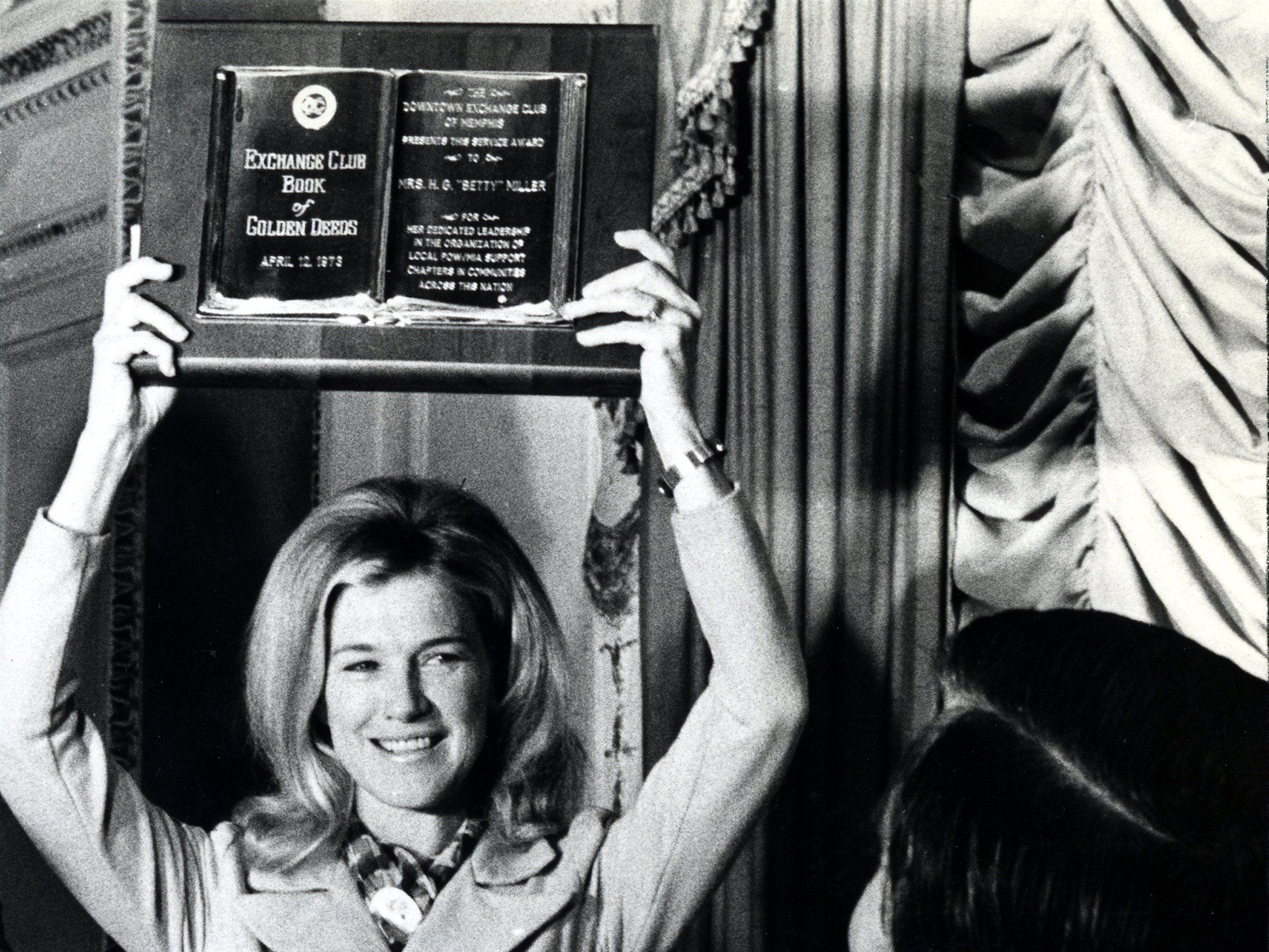 The Exchange Club's highest public-service award, the Book of Golden Deeds, went to Betty Miller, the petite, blond wife of Lt. Col. Henry G. Miller of Navy-Memphis on 12 Apr 1973.  The award was given for her work with POW and MIA support over a five year period.  Memphis Mayor Wyeth Chandler (Right) presented her with a City of Memphis Certificate of Achievement as well.  Richard Gardner / The Commercial Appeal files.
