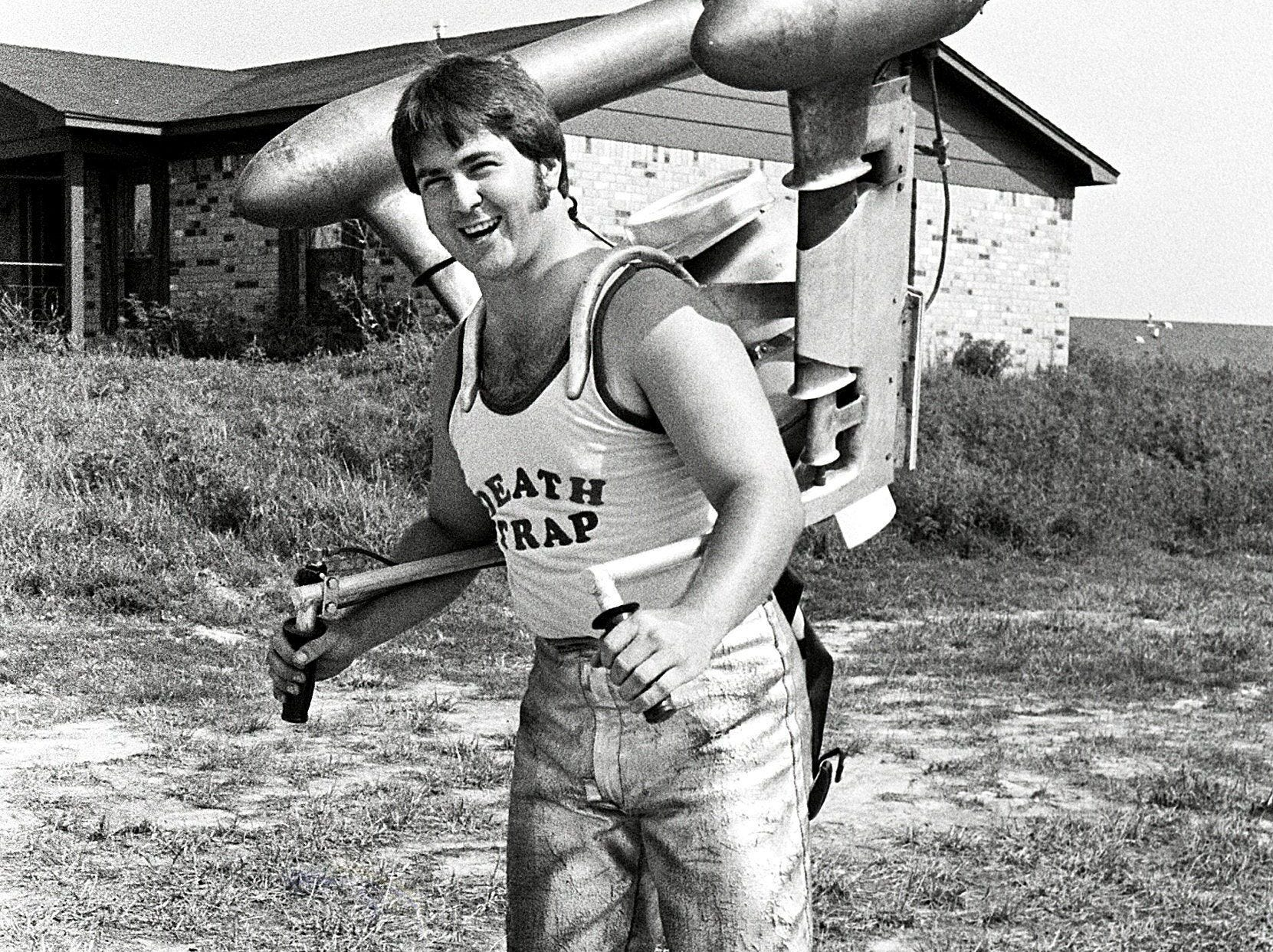 """Greg King, the 23-year-old """"Mississippi Mad Man"""", is the aspiring Evel Knievel of Walls, MS. The mild-mannered meat truck driver on weekdays hopes to zoom past Guinness world records on weekends with his roller skates and jet engine in August 1979. His equipment includes an 80-pound jet engine on his back and a pair of $500 roller skates on his feet."""
