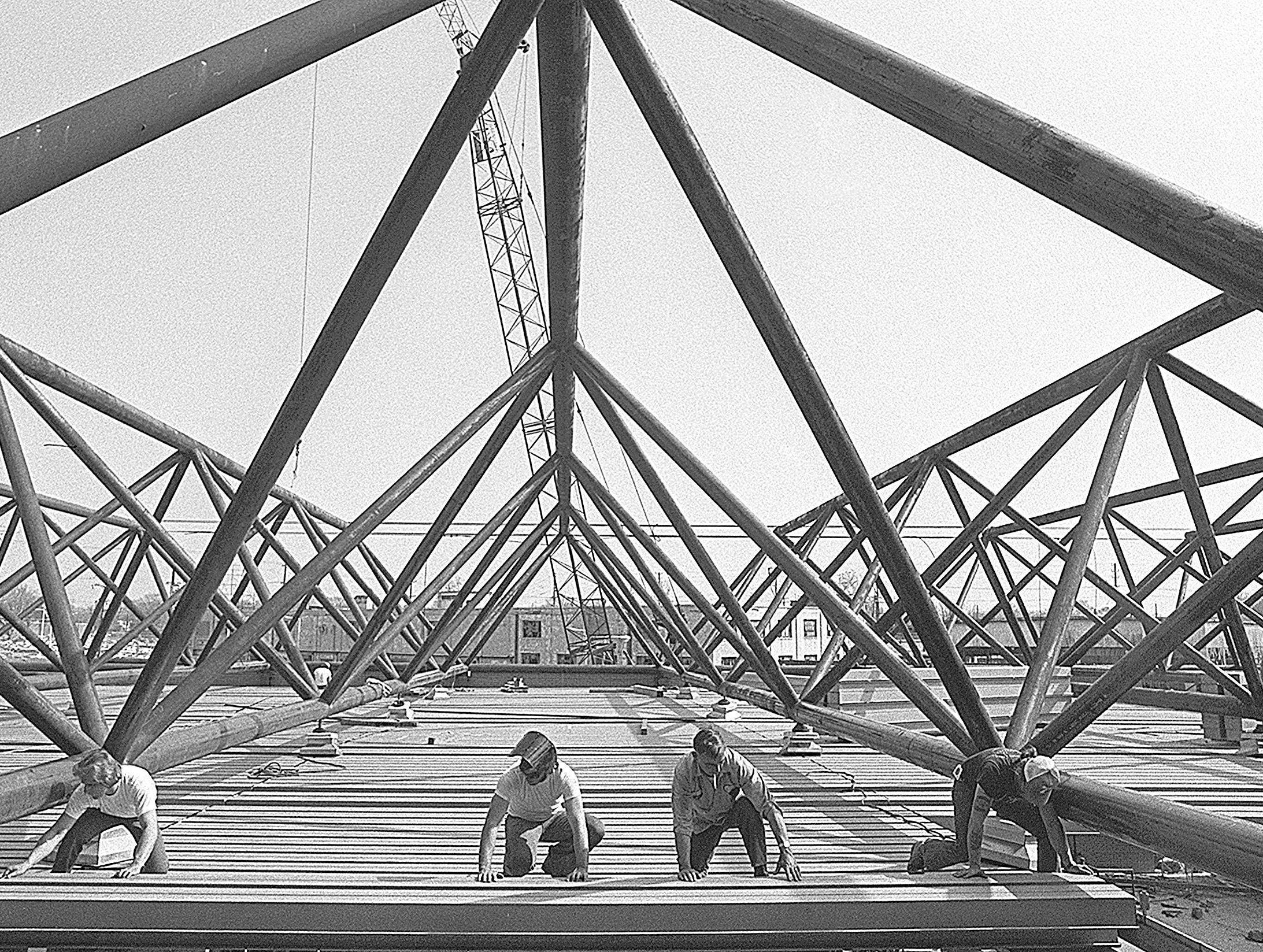 Workmen put the roof-ceiling on Shelby State Community College's gymnasium at Linden and Walnut in March 1977. From Left are: Scoffer Anderson, Bobby Williams, Pete Ashmore and Tony Spicer. They work for Metal Roof Decks, Inc. One building of the downtown campus has been in use for two years and four other structures were put into use the first of this year as other construction continued.