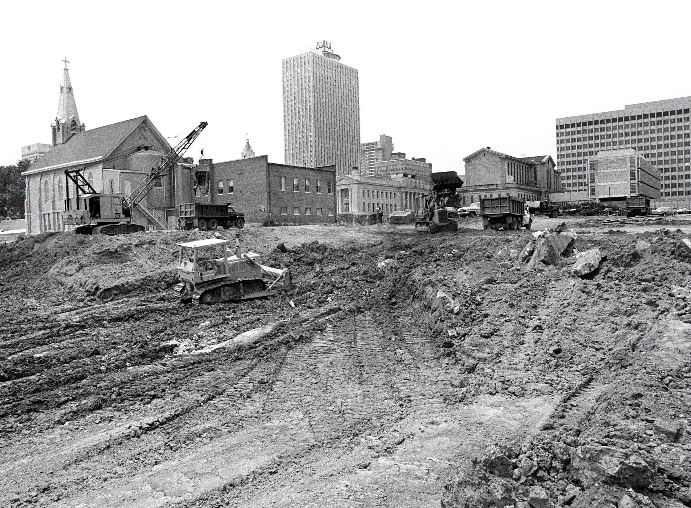 Excavation work is in full swing for the new $38.5 million Criminal Justice Complex at 201 Poplar Avenue on 5 July 1977 as seen in this view looking toward the southwest.  The center will include a 14-story court building and a 6-story detention center.  Groundbreaking occurred on 21 June, nine years after the project was first discussed.  It is expected to be completed in 24 to 30 months.  St. Peter's Catholic Church at 190 Adams Avenue is at far left.  Other buildings include (From Left) 100 North Main, the Shelby County Court House, the Shelby County Jail, the criminal courts building and the Shelby County Administration building.