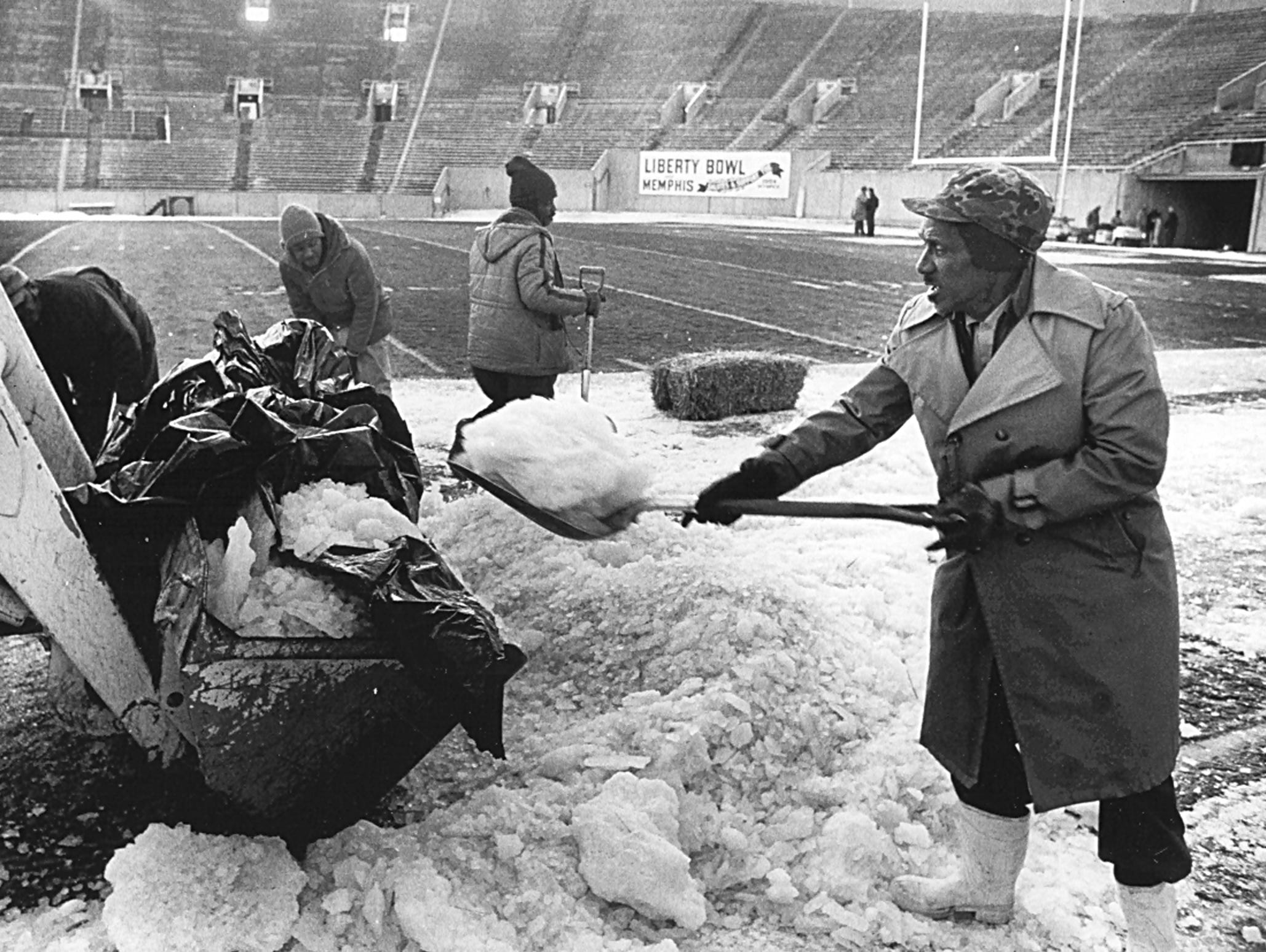 Park Commission employees cleared ice from the field at Liberty Bowl Memorial Stadium all day long on Dec. 29, 1983, in preparation for the annual postseason football game. George Powell (third from right), Roosevelt Golden (second from right) and Phillip Jackson (right) had been working since 7 in the morning. The photograph was taken at 4:30 in the afternoon. The two men at extreme left are not identified. They managed to get the job done and Notre Dame got their job done, beating Boston College 19 to 18.