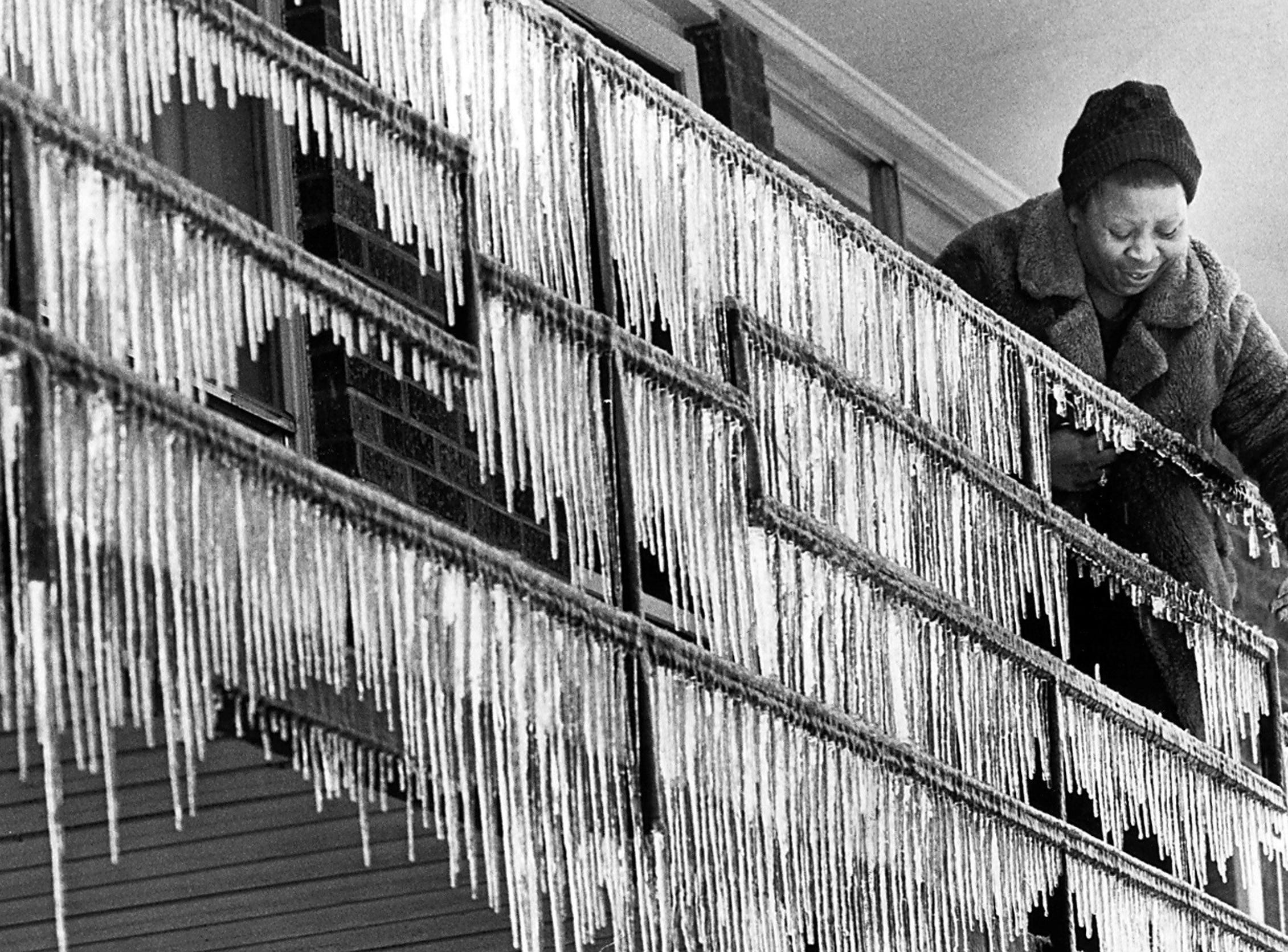 Mrs. Maude Scullark breaks icicles from the bannister at her sister's apartment on Tillman on 12 Jan 1978. She lives in southwest Memphis, but was stranded overnight due to the icy conditions.