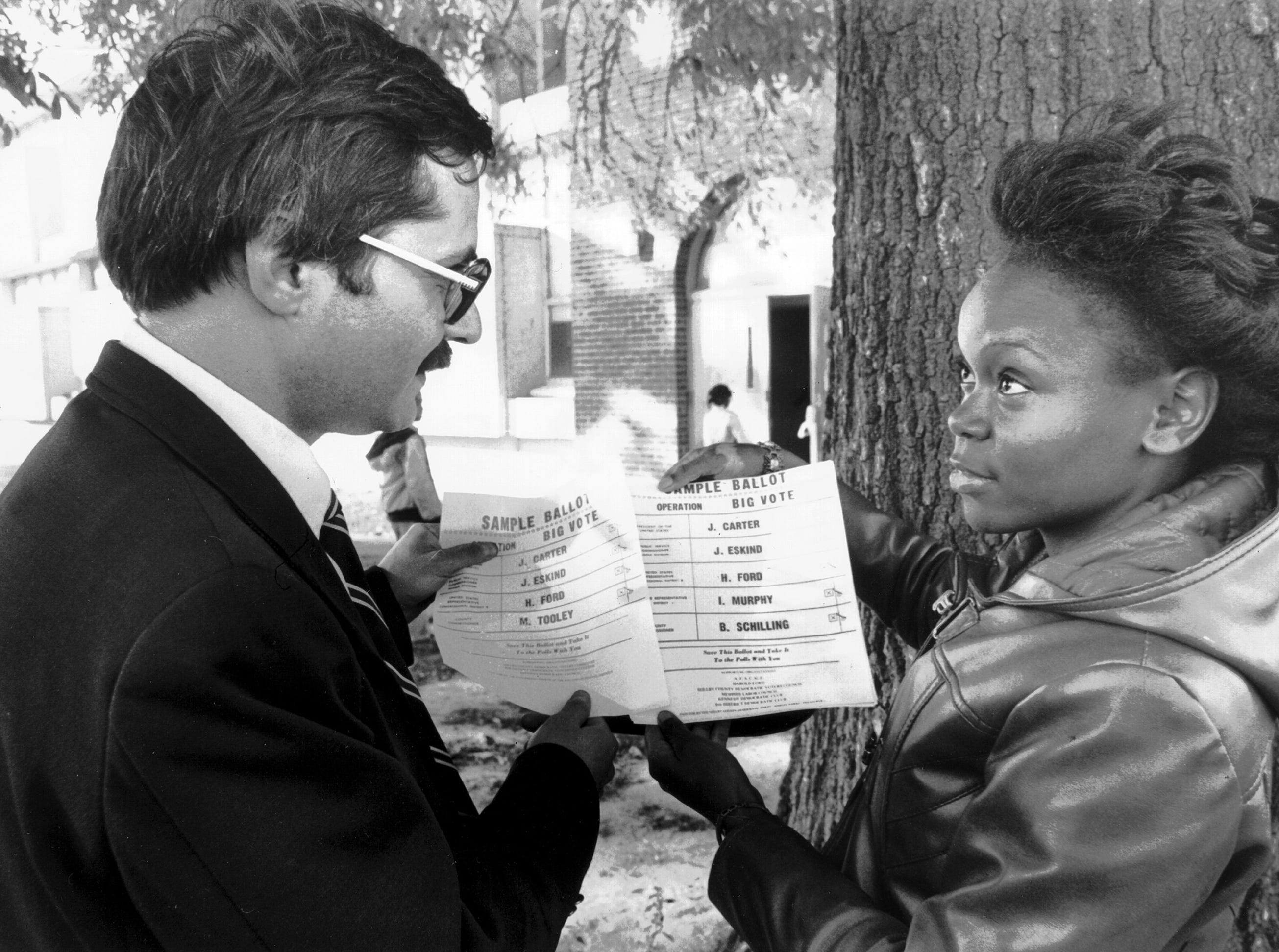 Peter Brown (left) and Bobbie Jean Moody examine sample ballots distributed in Ward 2 during elections held on November 4, 1980. The Democratic party routinely distributes sample ballots to voters, listing the names of their candidates; however, during this election, someone distributed bogus sample ballots that listed the names of some Republicans. It was unknown who distributed the bogus pages.