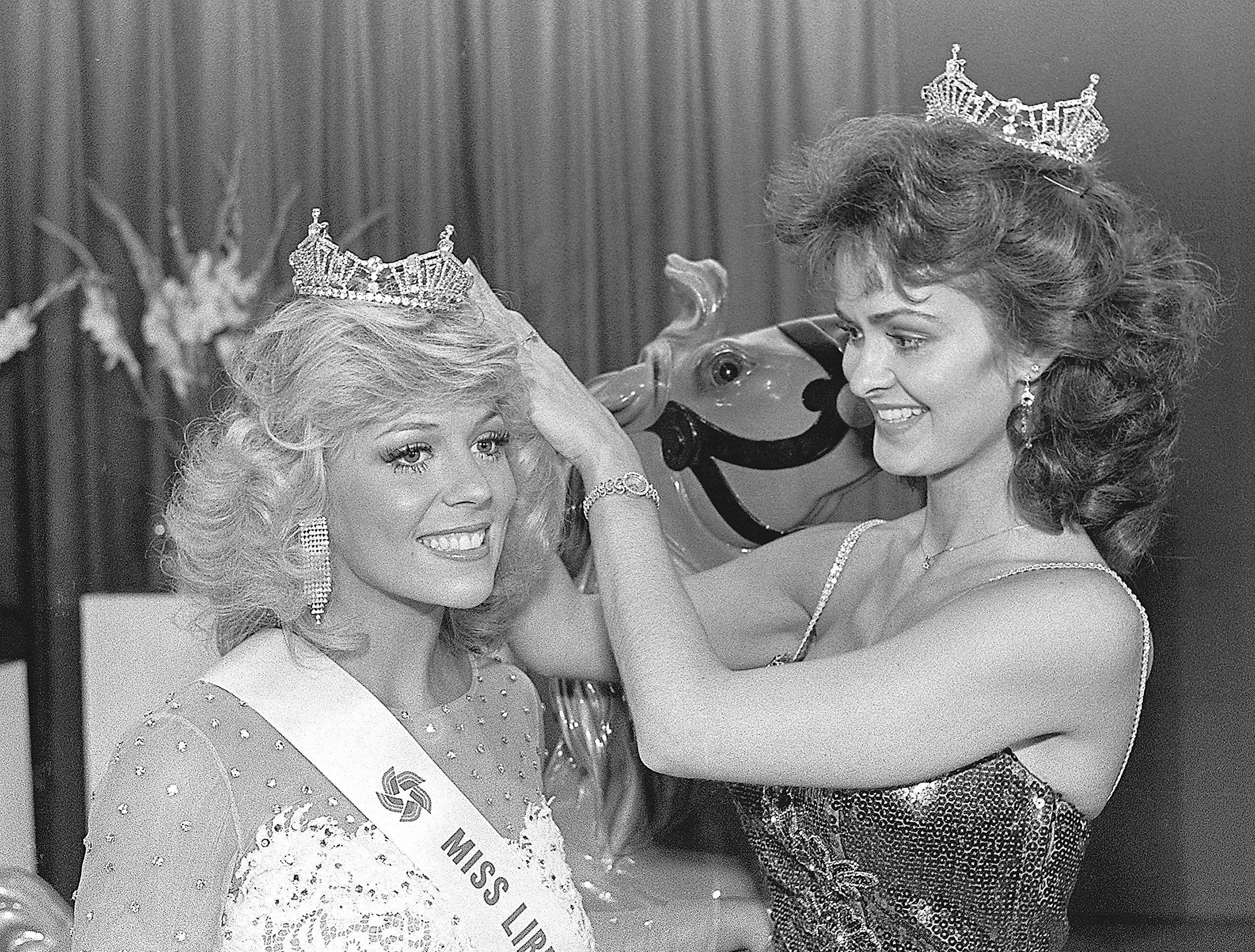 Sharon Russell, left, gets a hand from her predecessor, Susan Gail Biffle as she is crowned Miss Libertyland 1985 on 1 July 1984. First runner-up was Kris Beasley and second runner-up was Robbie McDaniel. Miss Russell, 21, daughter of Mr. and Mrs. Bobby Russell of Raleigh, is a senior studying communications at Memphis State University. She was 1983 Miss Memphis State.