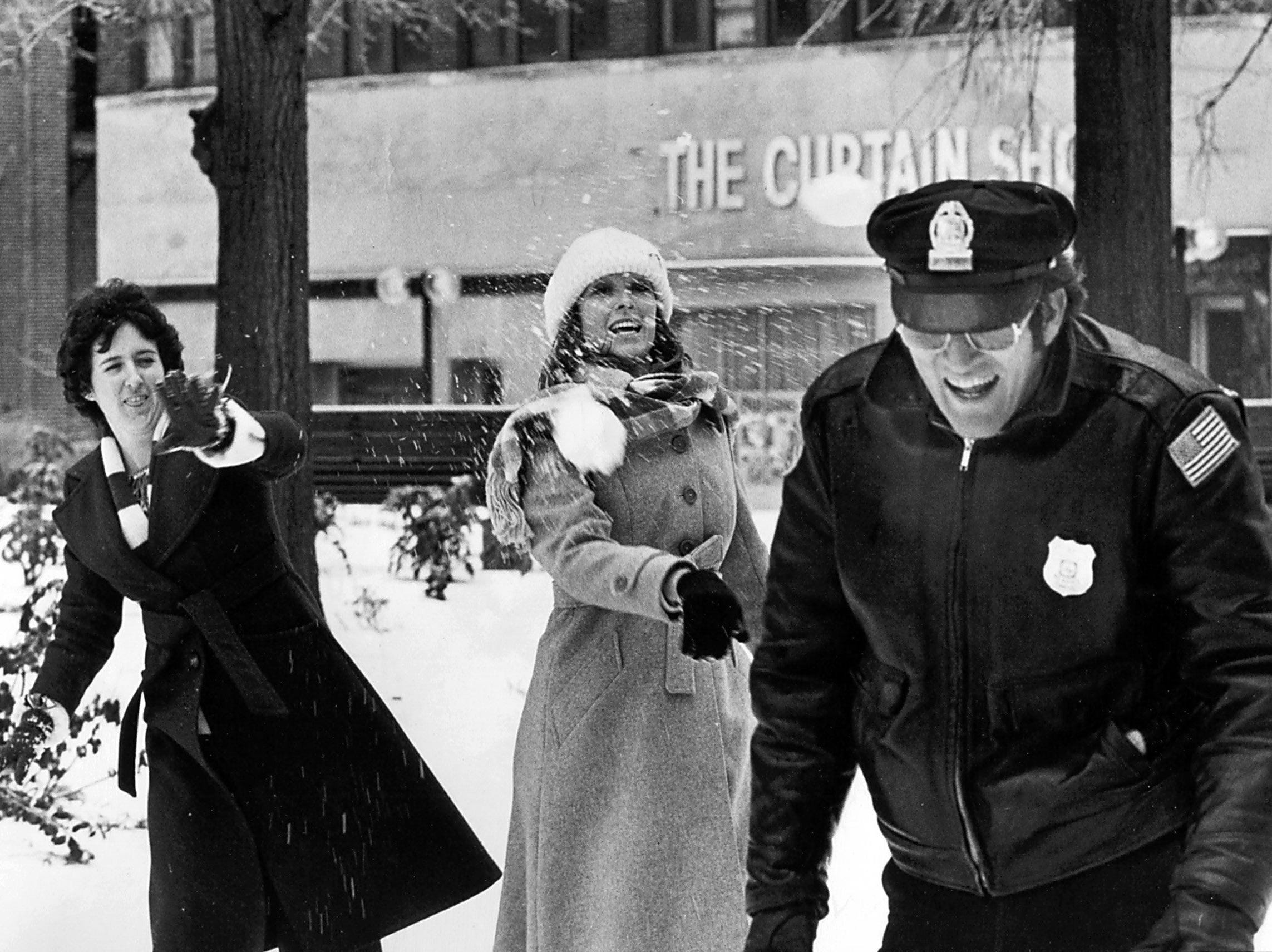 Memphis Policeman W.L. Sanders (Right) got a volley of snowballs from Pam Wortham (Left) and Cathy Reves (Center) during the lunch hour on 12 Jan 1978. They work at W.R. Grace.