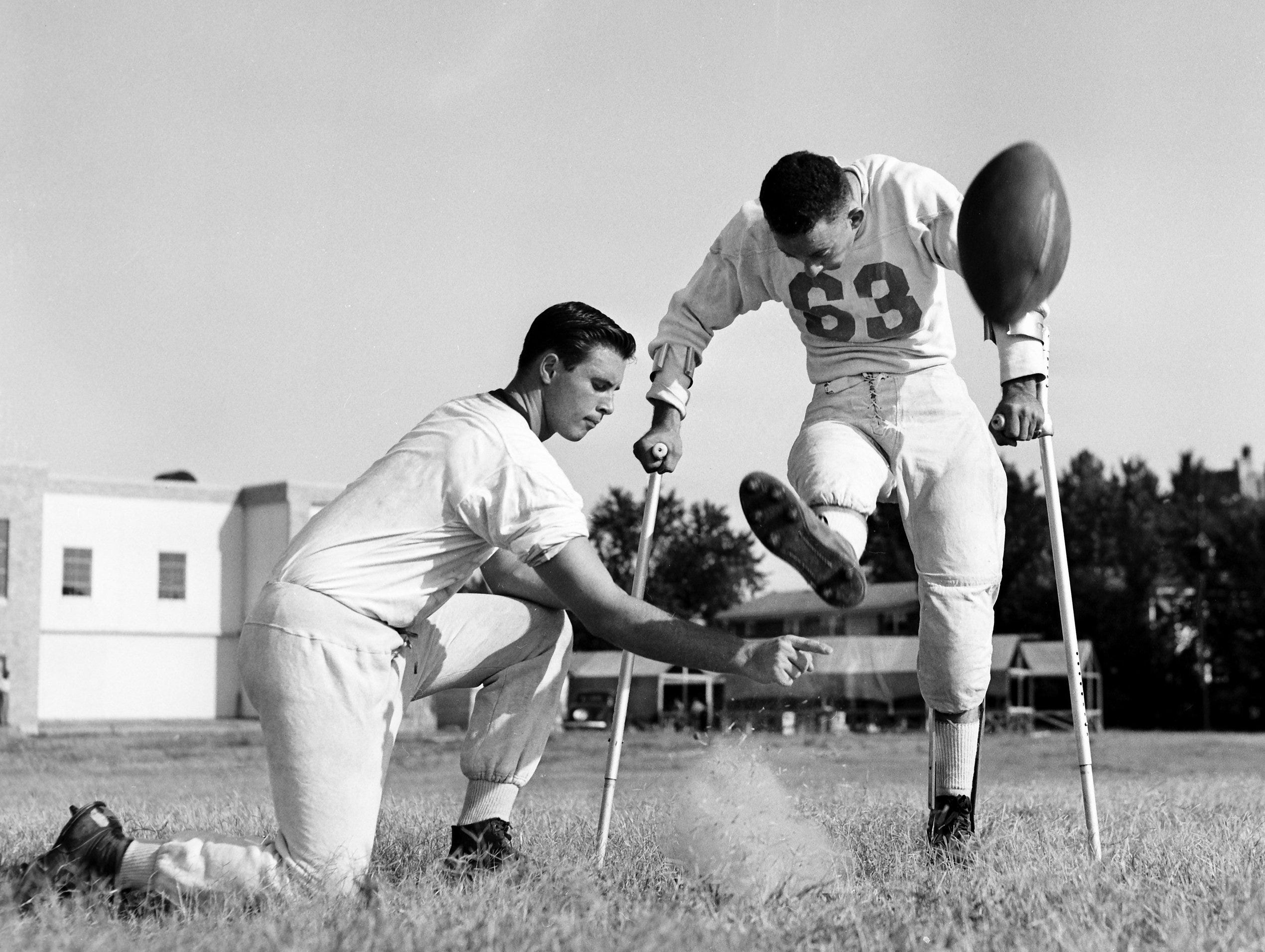 Billy Gillespie, stricken with polio before football season in 1952, is back in uniform the first week of September 1953.  With the aid of crutches and braces on his legs, Billy is out every afternoon practicing extra points at Catholic High.  Here Billy boots one as George Wade holds.