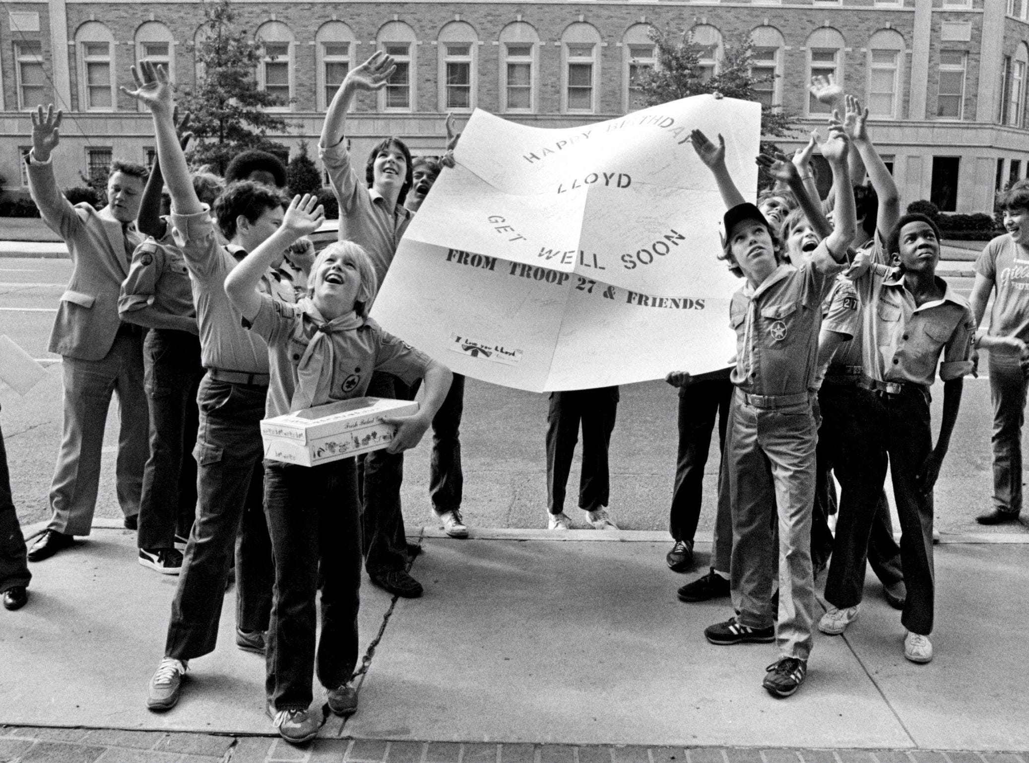 "Members of Boy Scout Troop 27 in Bartlett gather outside Methodist Hospital on Oct. 10, 1982, to wish their scoutmaster well on his 51st birthday. Lloyd Adams, who has been the troop's scoutmaster since 1948, was having surgery. He said the big card ""made my day."" He served as scoutmaster for the fathers of some of the Scouts holding the big card."