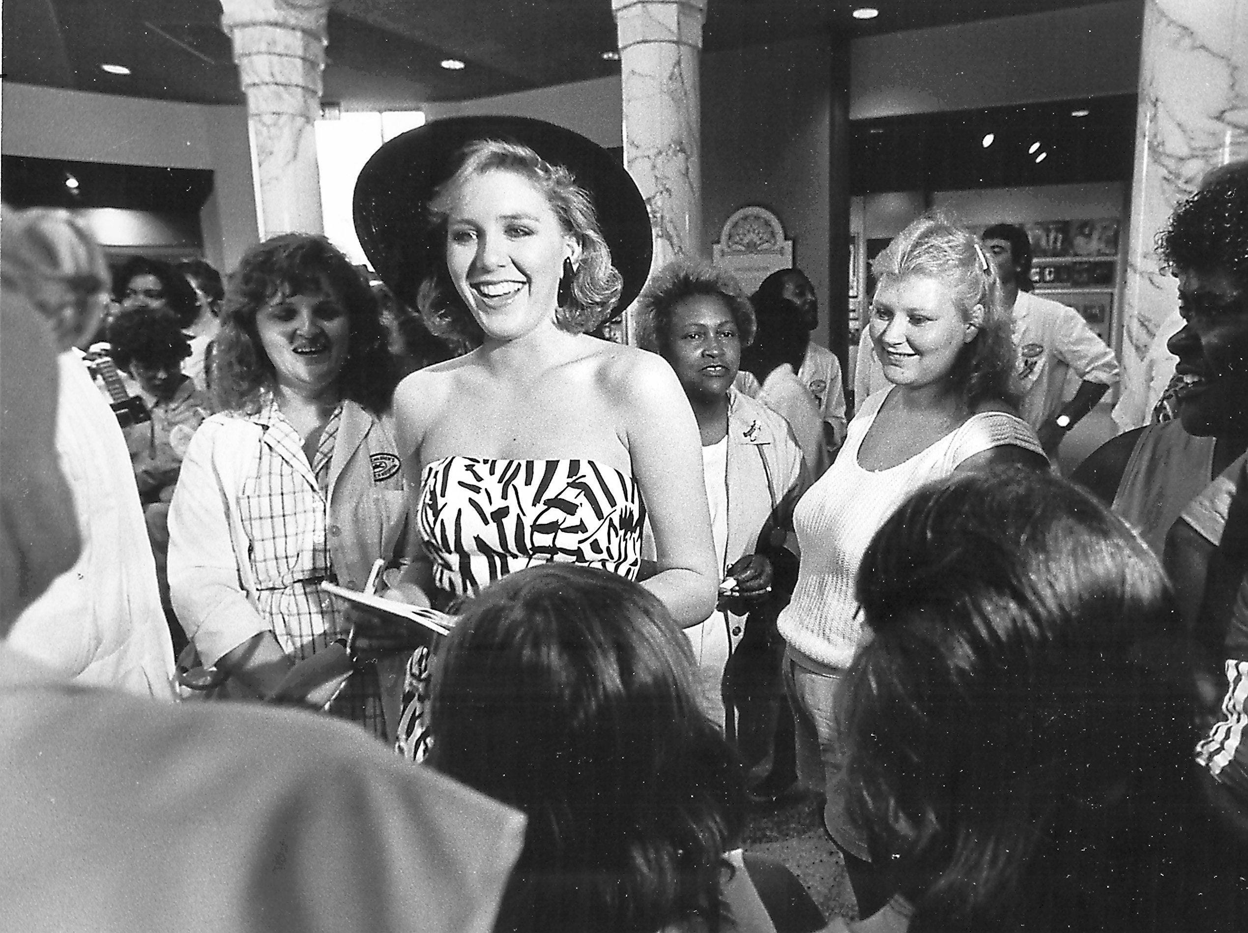 Miss America Kellye Cash signs autographs for staff and patients at St. Jude Children?s Research Hospital on 29 July 1987. She was visiting the hospital with founder Danny Thomas, Michael Jordan, Archie Manning and others in connection with the Federal Express St. Jude Classic Golf Tournament.