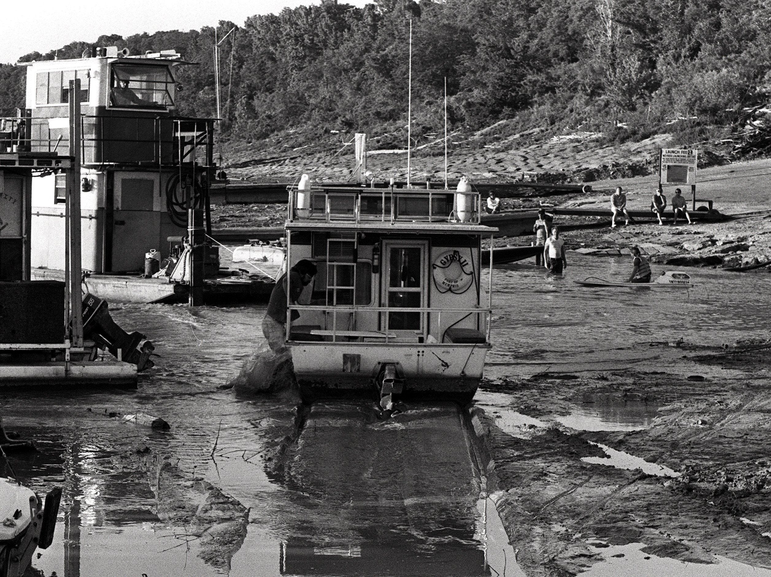 A fast drop on the Mississippi River had six pleasure boats in the mud and another half-dozen blocked off from the river in their slips at Buttercup Marina on McKellar Lake on 4 June 1988. The towboat Robin McCarter pulls the Gypsy II through mud to open water after the lake level dropped rapidly.