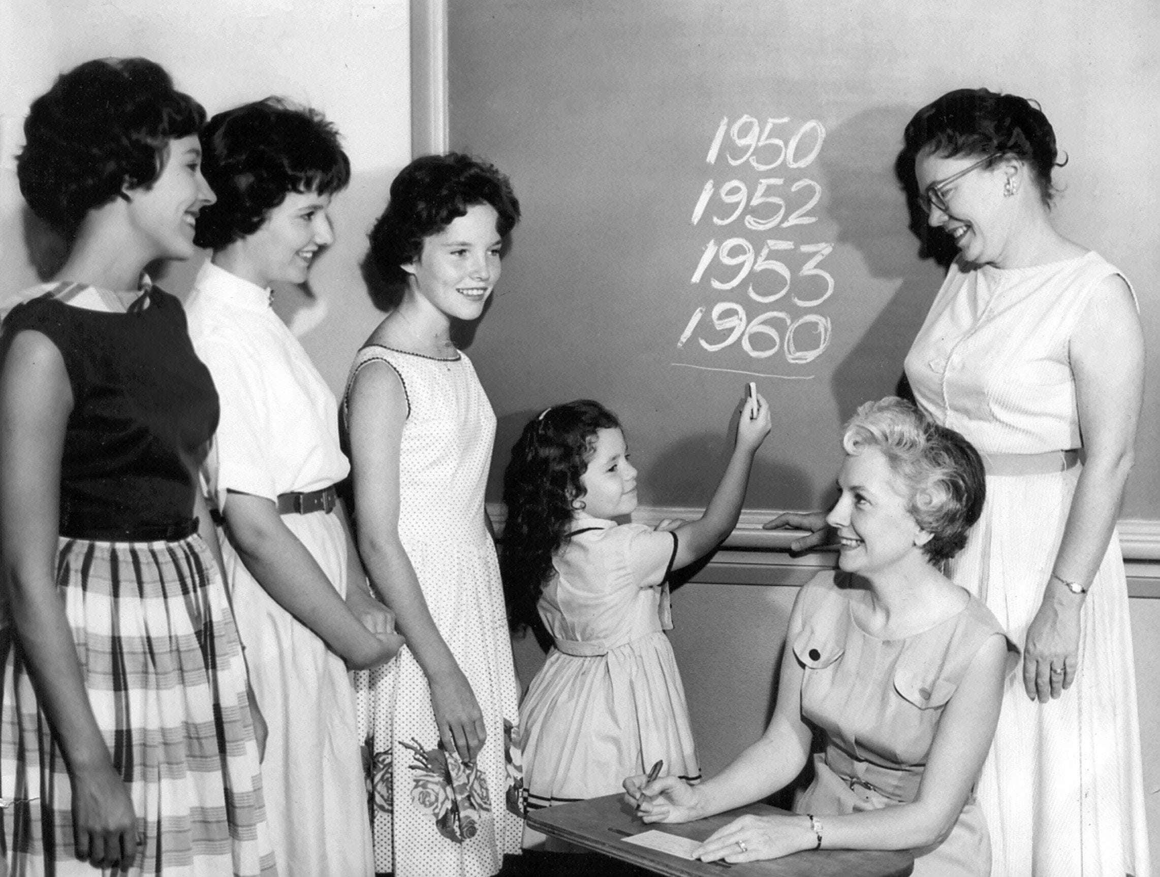 Mrs. Dave M. Williams, seated, of 175 Picardy Place hoped on 29 Aug 1960 that Mrs. Ann Daws, first-grade teacher at East, would draw four of a kind when pupil assignments are dealt out as she completed registering 6-year-old Debbie Williams. Mrs. Daws taught Debbie?s three sisters, from left, Bonnie, 16, Joanie, 14, and Patsy, 13, when they were first-graders. Oh, and by the way, Debbie was in Mrs. Daws? class, too.  Photo for The Commercial Appeal by