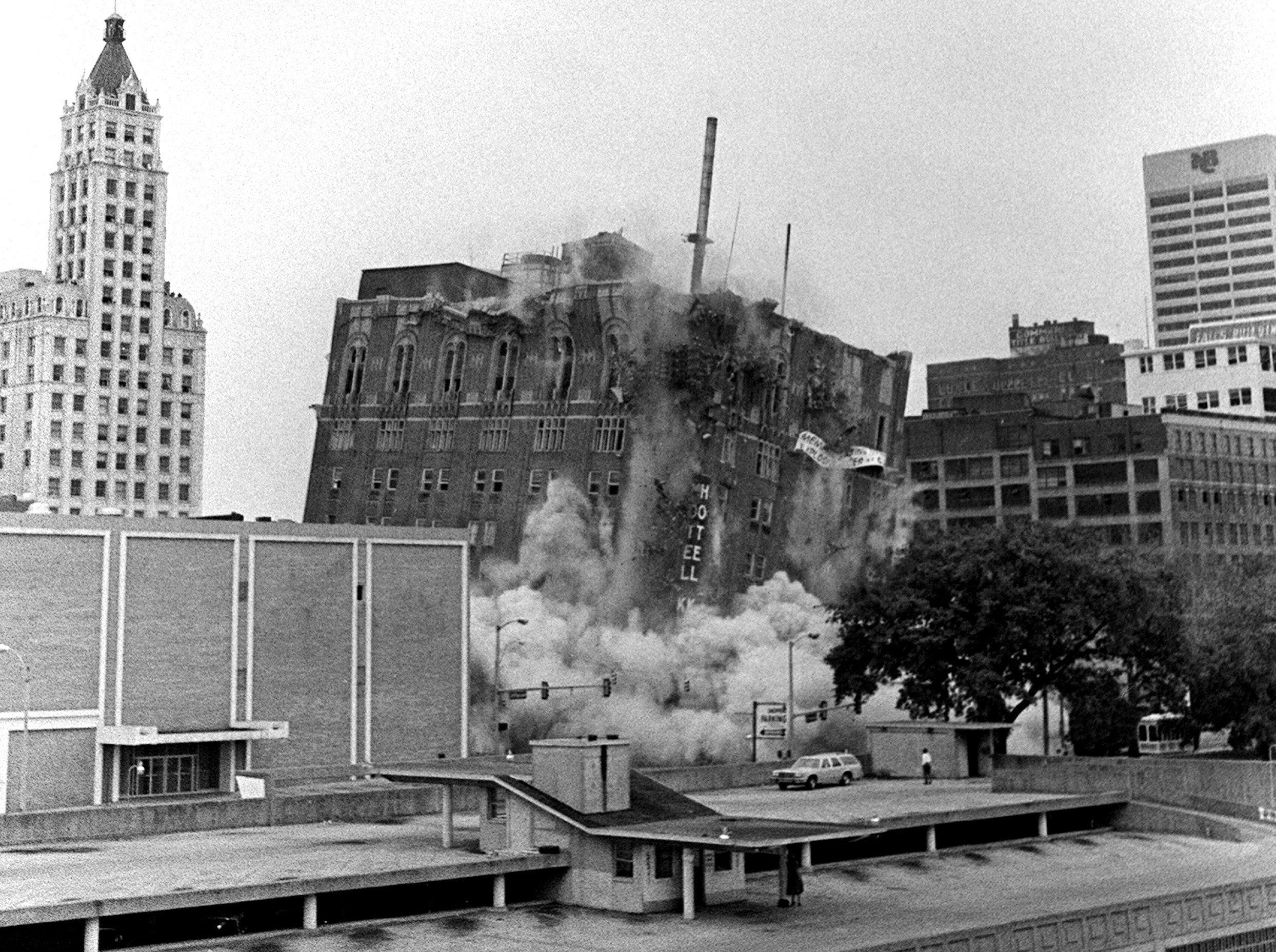 The Hotel King Cotton crumbles after demolition charges are set off on 29 Apr 1984. The Lincoln American Tower is at left and One Commerce Square is at far right. Morgan Keegan Tower stands on the site today.