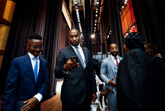 Lee Harris (middle) takes a phone call after being sworn in as the new mayor of Shelby County during a ceremony Thursday afternoon at the Cannon Center of the Performing Arts in Memphis.