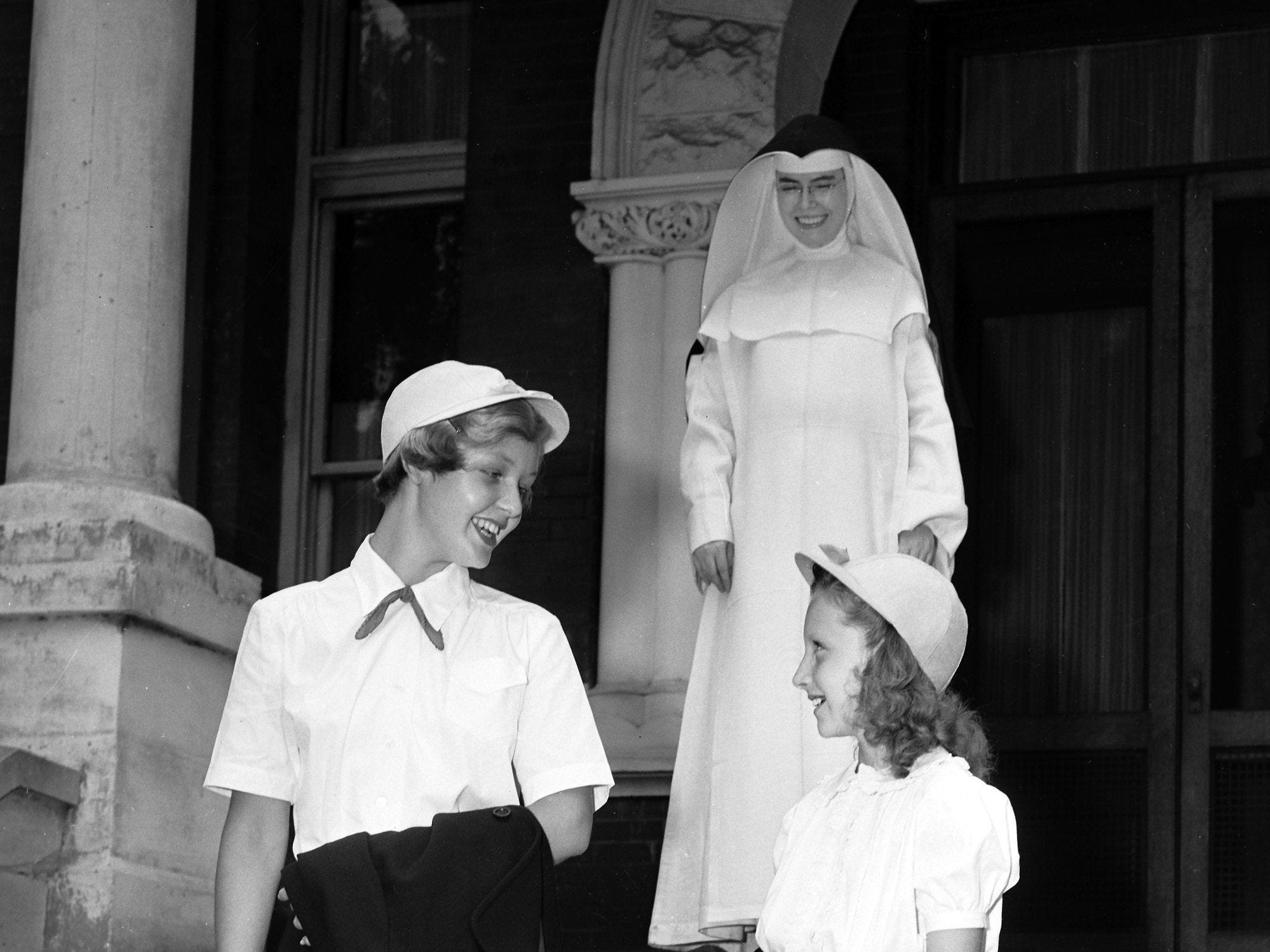 Margaret Montedonico, left, 15-year-old daughter of Mr. and Mrs. Louis Montedonico of 1637 York Avenue, and Nikki Lentz, 10, daughter of Mr. and Mrs. H.M. Lentz of Ellendale, model uniforms pupils of St. Agnes Academy will wear in the fall. Sister Suzanne, school principal, looks on approvingly on June 29, 1951.