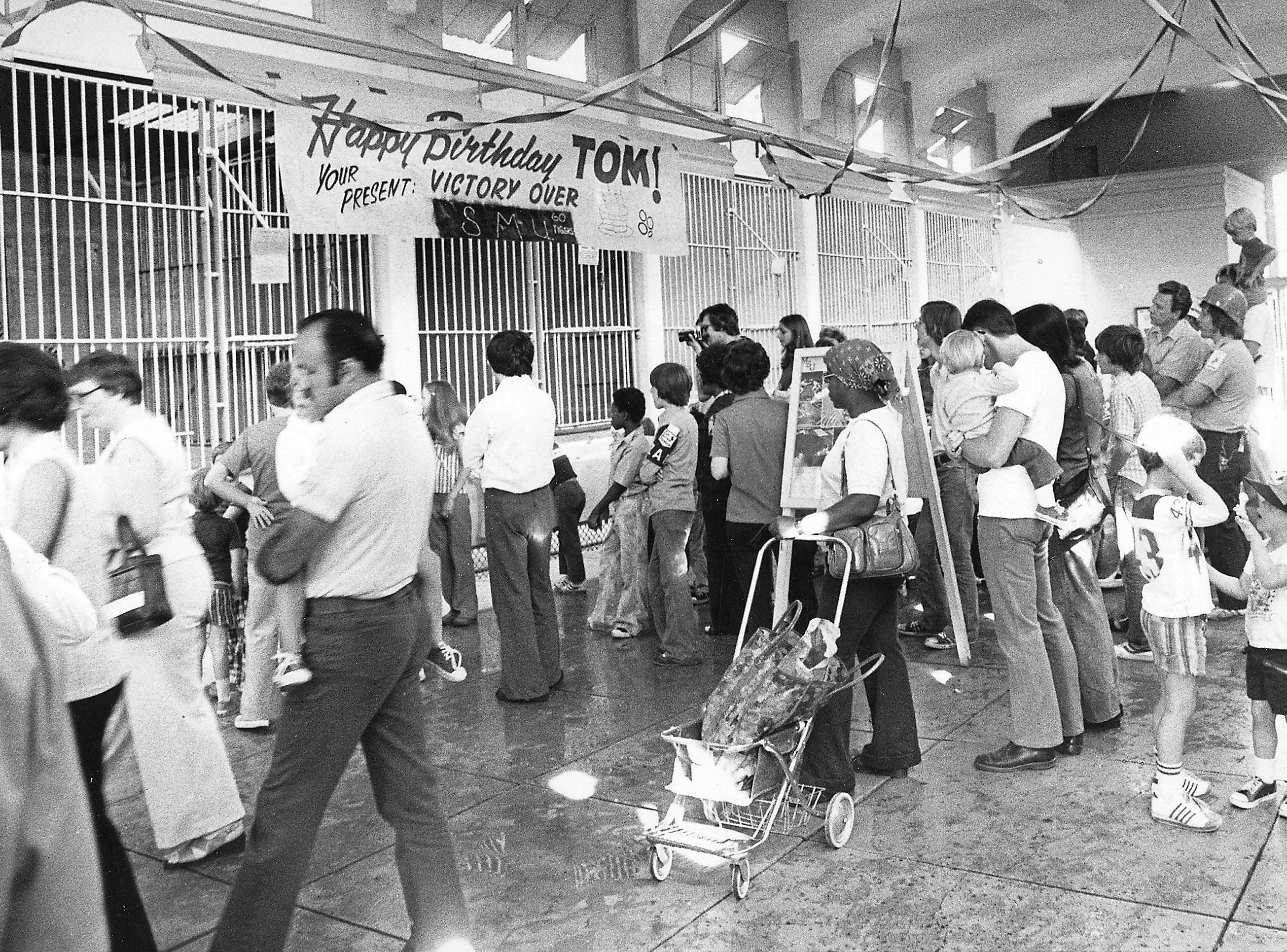 """Memphis State University fans turn out at the Memphis Zoo to wish Tiger mascot """"TOM"""" a happy fourth birthday on Sept. 25, 1976. The party included a cake, candles, a 16-foot card, three gift footballs and about 150 well-wishers. The party was arranged primarily by TOM's keeper Louie Bell and Cecil Sowell, vice president of the Highland Hundred booster club."""