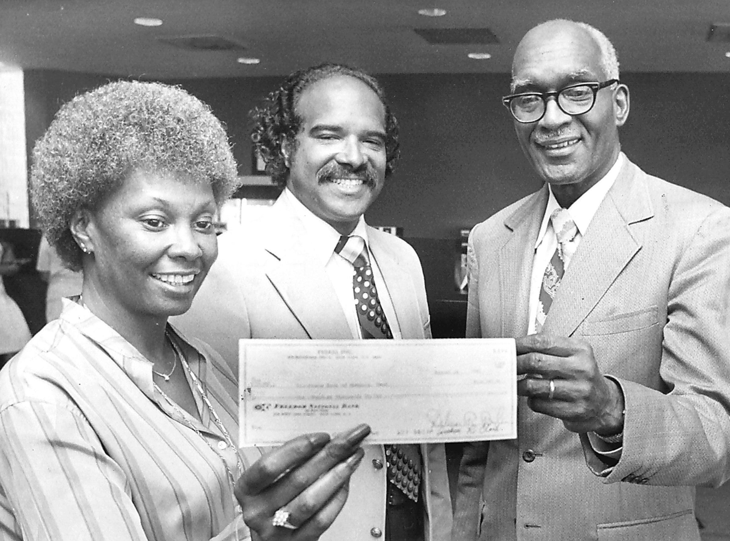 Elaine Williams (Left), loan officer of Presbyterian Economic Development Corp. of New York, holds a check for $100,000 that was deposited in Tri-State Bank of Memphis as venture capital for businesses setting up shop on Beale Street on 21 Aug 1980. George B. Miller (Center), executive director of Beale Street Development Corp and Tri-State president and chief executive officer Jesse Turner look on. Restoration of the historic street continues between Third and Fourth.