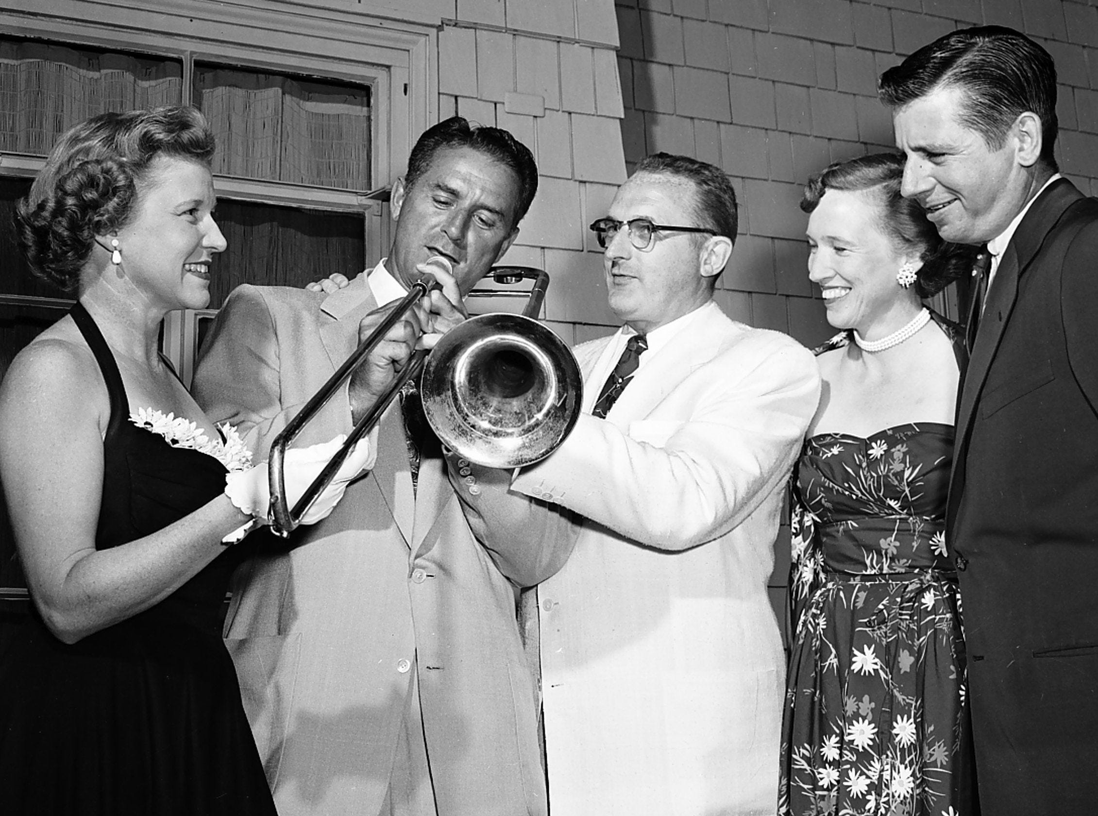 James W. Moore, second left, new entertainment chairman for the University Club, receives an impromptu trombone lesson from Tommy Dorsey, center, who was a special guest at the club?s al fresco buffet supper and dance on 13 June 1953. Looking on were Mrs. Moore, left, and Mr. and Mrs. George W. Humphreys.