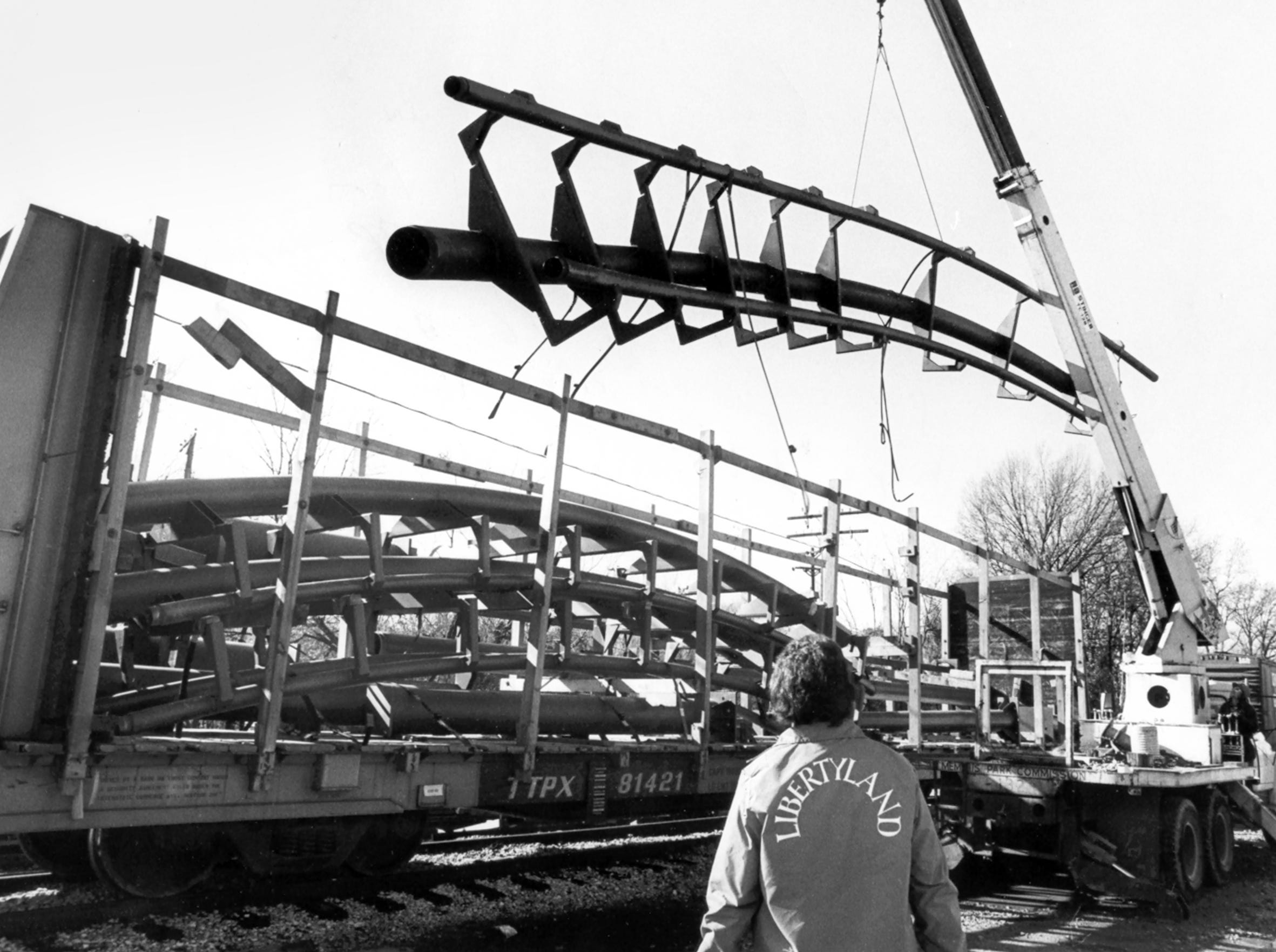 """Ride mechanic Joe Spuryer watches as """"The Revolution"""" is unloaded at the Southern Railroad yard on Dec. 14, 1978. The new $1.7 million ride for Libertyland required 16 cars to deliver the ride and parts. Workers were hoping to finish construction by the park's yearly opening in March."""