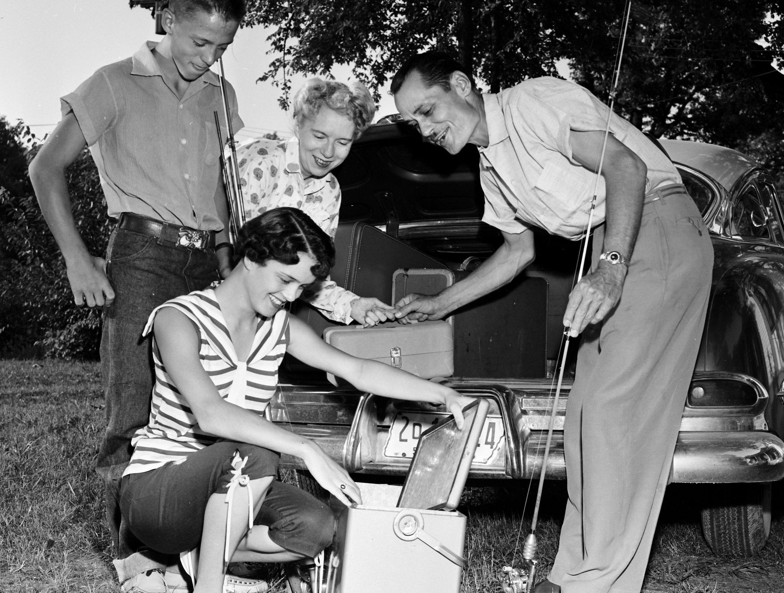 Joe May, left, 13-year-old champion of the Mid-South Junior Fishing Rodeo, is now enjoying his prize ? a week?s all-expenses-paid trip to Watts Bar Reservoir near Chattanooga during July 1955. Joe checks his equipment with his mother, Mrs. J.C. May, and his father, J.C. May. Sister Dolores, squatting, is vacationing with the champ and his parents.