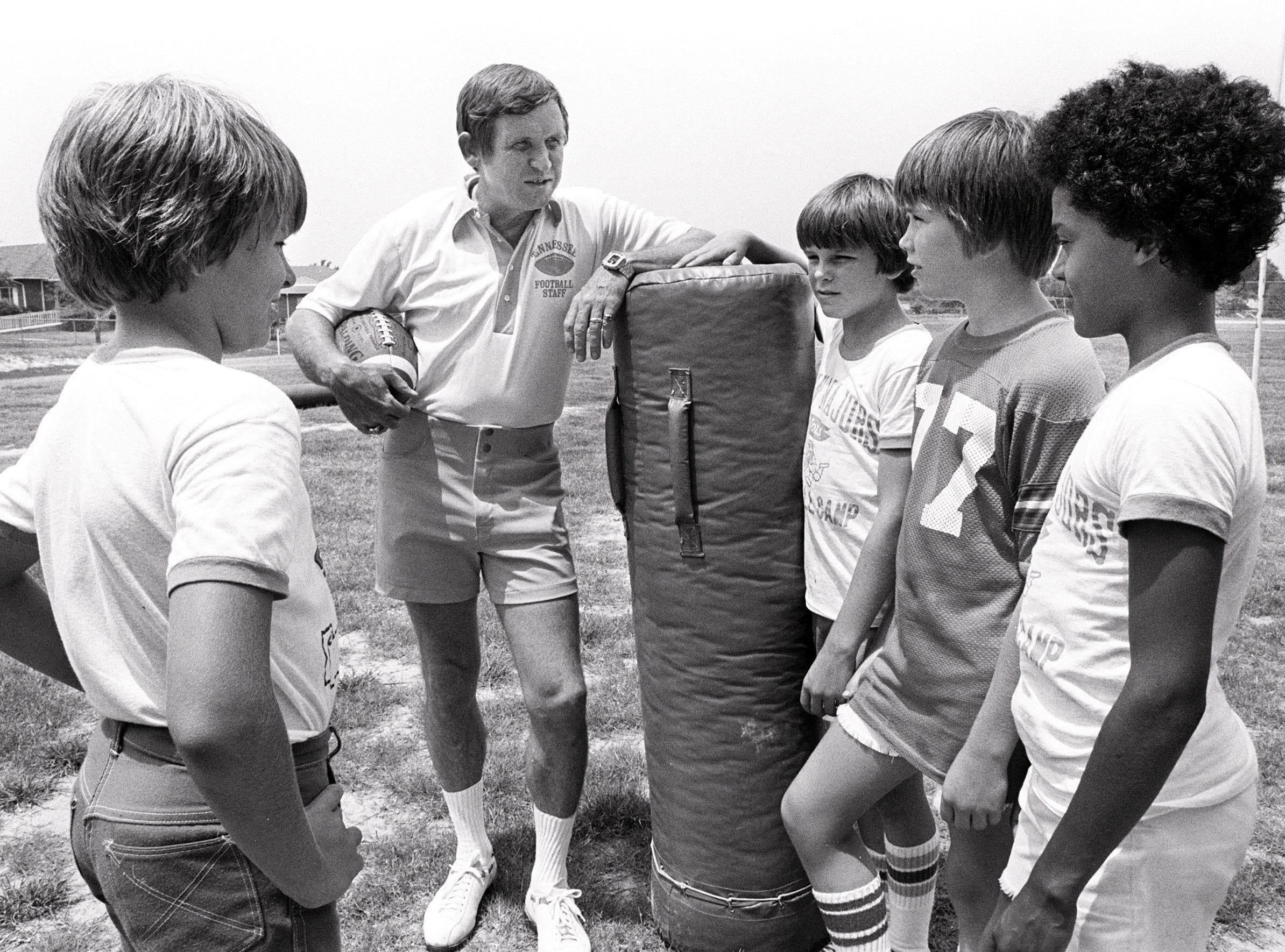 The topic is football in July 1977 and the man in the spotlight is University of Tennessee head coach Johnny Majors.  Giving their attention to the subject are (From Left): Michael Rush, Tim Hutchinson, Briar Borr and Hammond Gibson.
